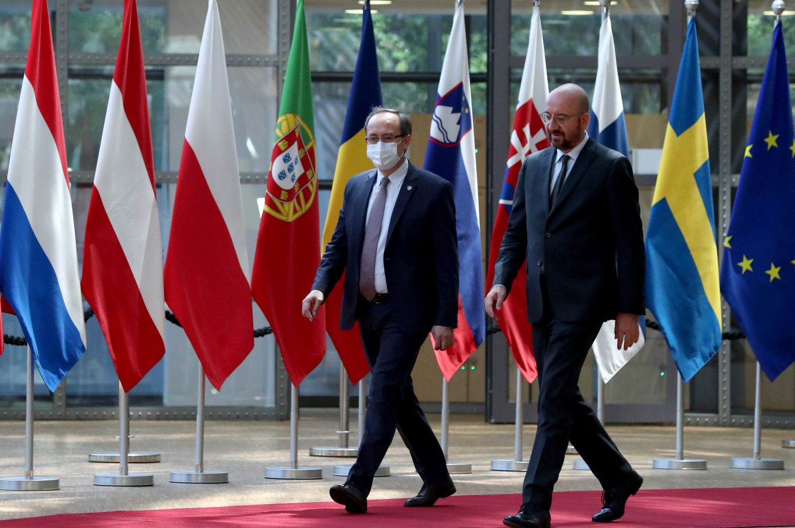 Kosovo's Prime Minister Avdullah Hoti (L) is welcomed by European Council President Charles Michel prior to a meeting at the Europa building, Brussels, June 25, 2020. (AP Photo)