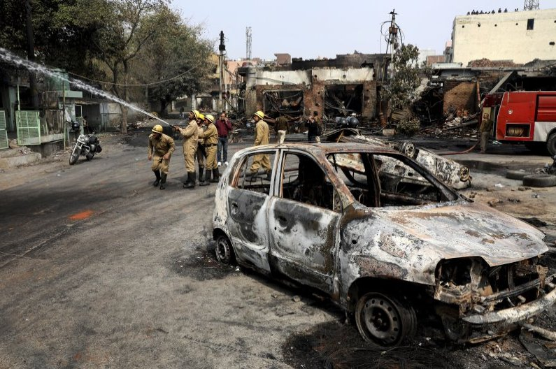 Firefighters douse a fire at Gokulpuri tire market, New Delhi, India, Feb. 26, 2020. (AP Photo)