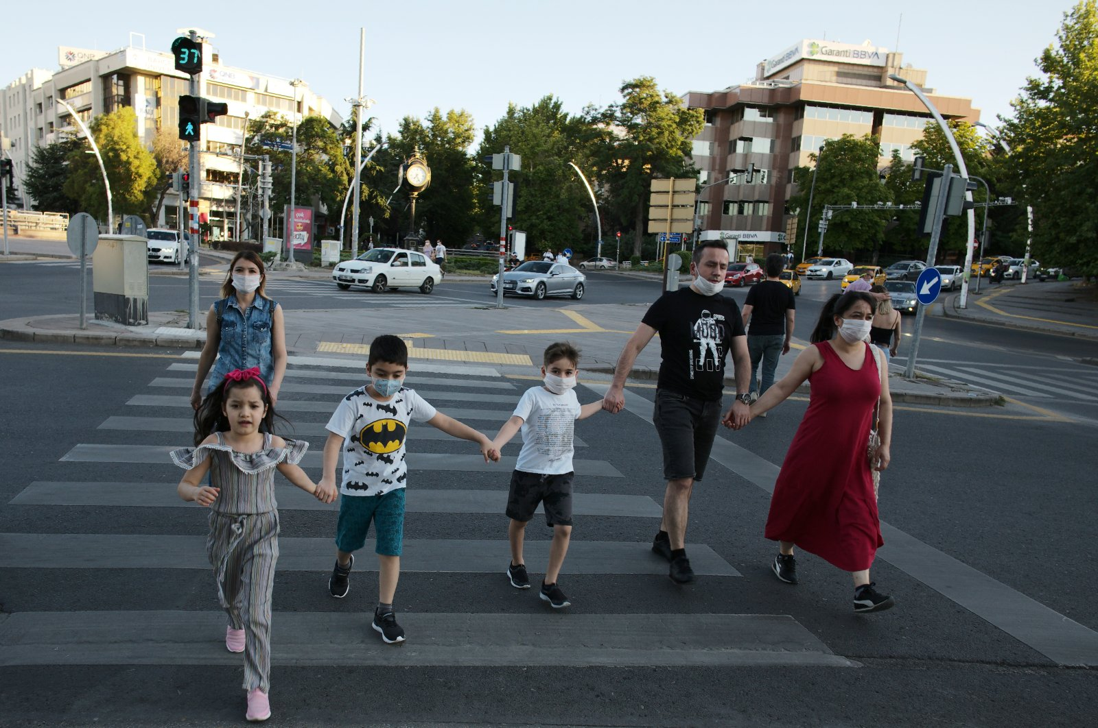 People wearing face masks to protect against the spread of coronavirus, cross a main street, in Ankara, July 11, 2020. (AP Photo)