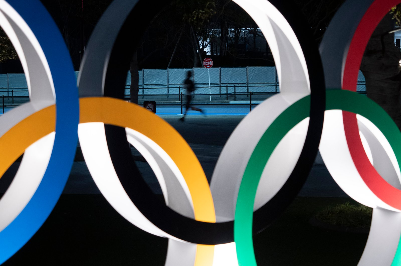 A man jogs past the Olympic rings in Tokyo, Japan, March 30, 2020. (AP Photo)
