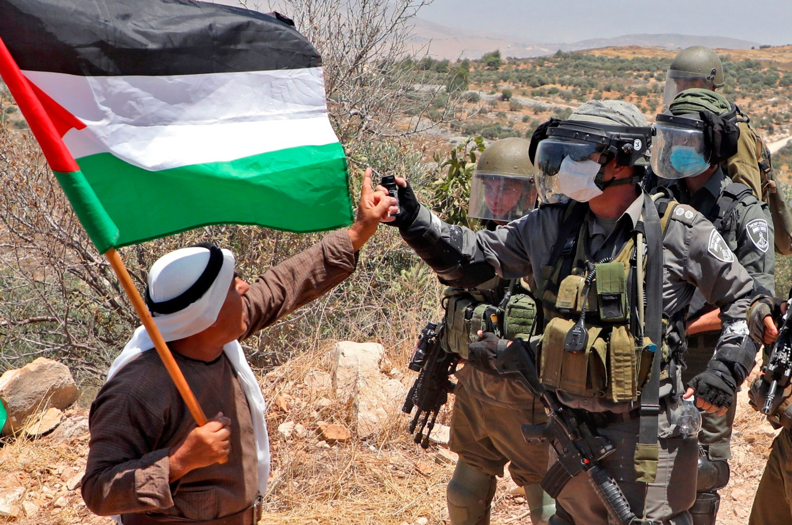 A Palestinian demonstrator confronts an Israeli border guard during a protest against Jewish settlements and Israel's planned annexation of parts of the Israeli-occupied West Bank, in the town of Asira Shamaliya near the West Bank city of Nablus on July 17, 2020. (AFP Photo)
