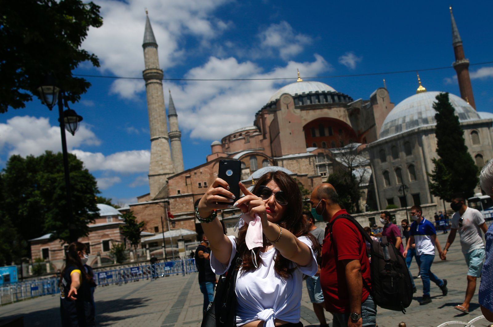 A woman uses her mobile to take a selfie outside the now closed Byzantine-era Hagia Sophia, one of Istanbul's main tourist attractions in the historic Sultanahmet district of Istanbul, July 11, 2020. (AP Photo)