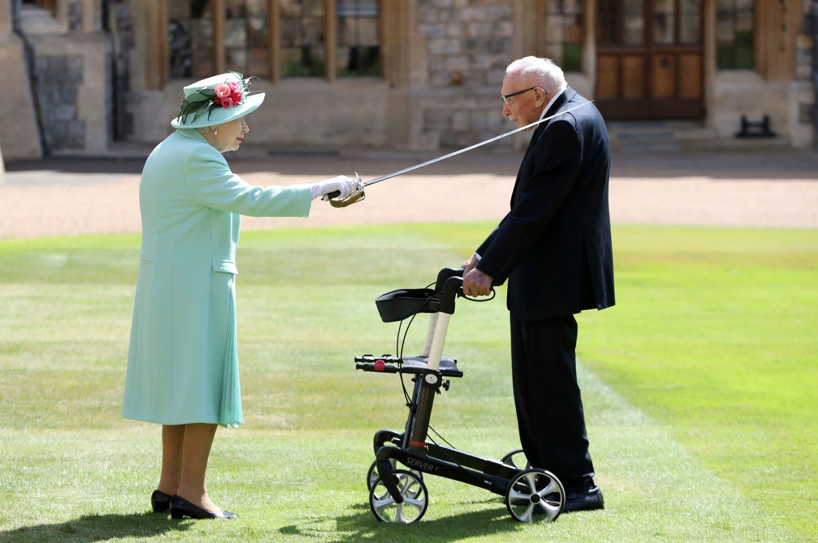 Captain Sir Thomas Moore receives his knighthood from Britain's Queen Elizabeth, during a ceremony at Windsor Castle in Windsor, England, July 17, 2020. (AP Photo)