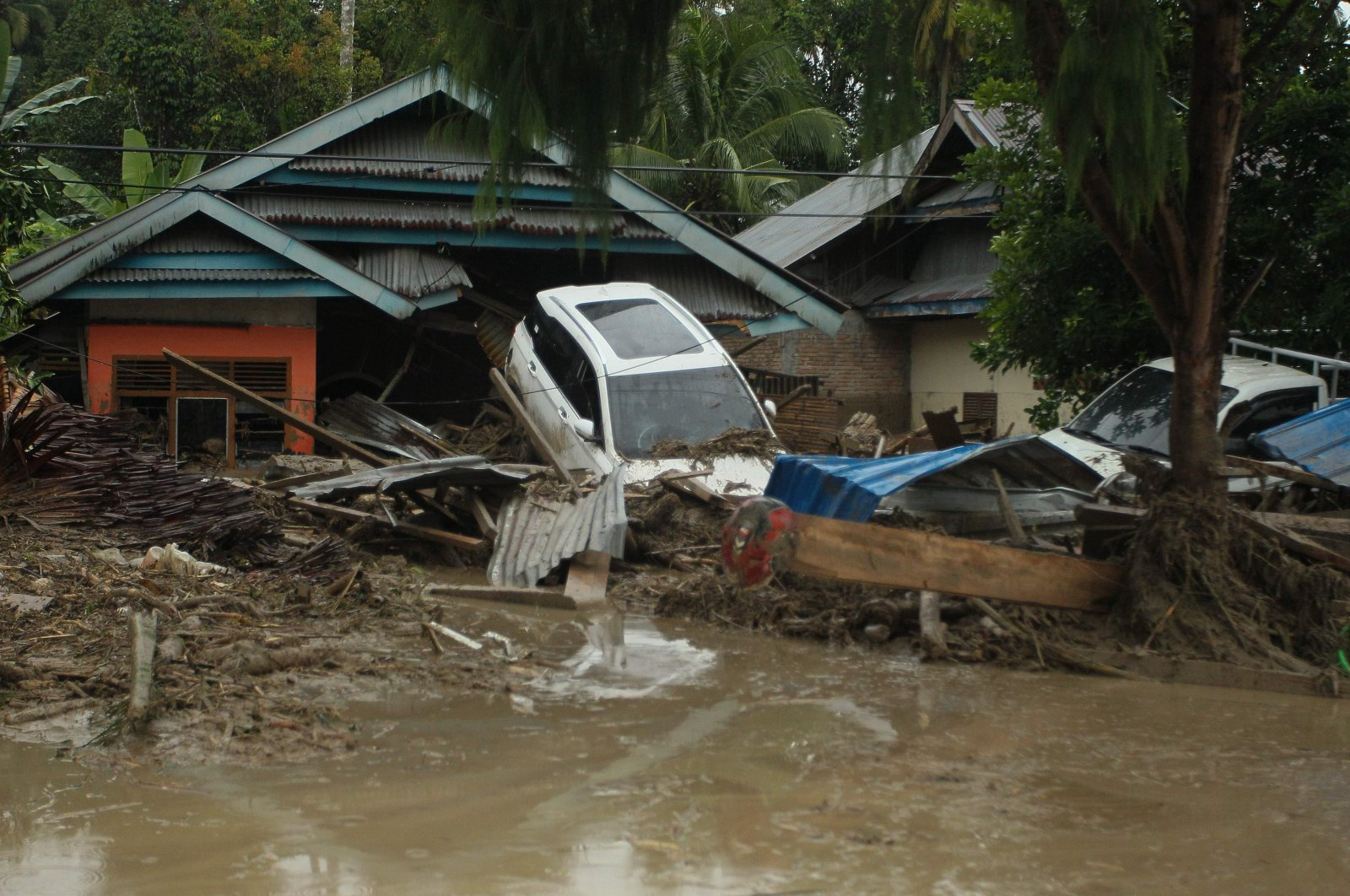 A general view shows vehicles swept away by flash floods next to houses in Radda village in North Luwu regency, South Sulawesi on July 14, 2020. (AFP Photo)
