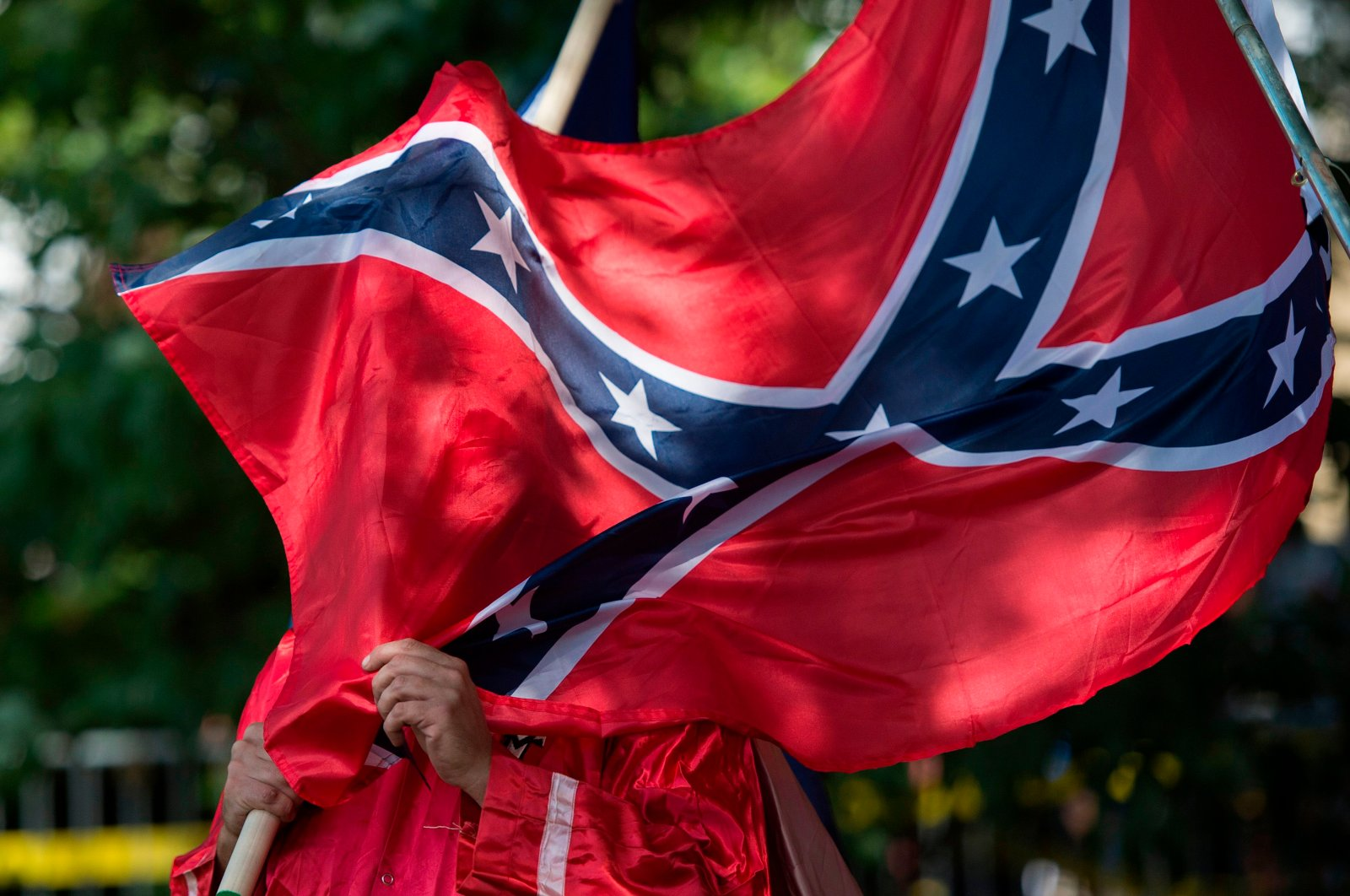 A member of the Ku Klux Klan holds a Confederate flag over his face during a rally, calling for the protection of Southern Confederate monuments, in Charlottesville, Virginia on July 8, 2017. (AFP Photo)