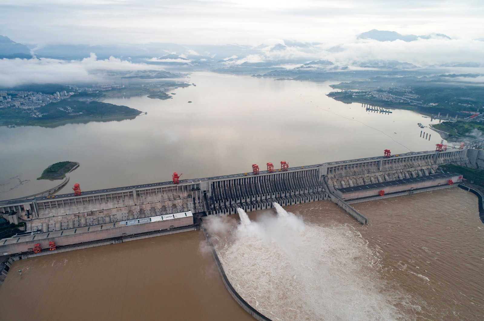 In this photo released by China's Xinhua News Agency, water flows out from sluiceways at the Three Gorges Dam on the Yangtze River near Yichang in central China's Hubei Province, Friday, July 17, 2020. (Wang Gang/Xinhua via AP)
