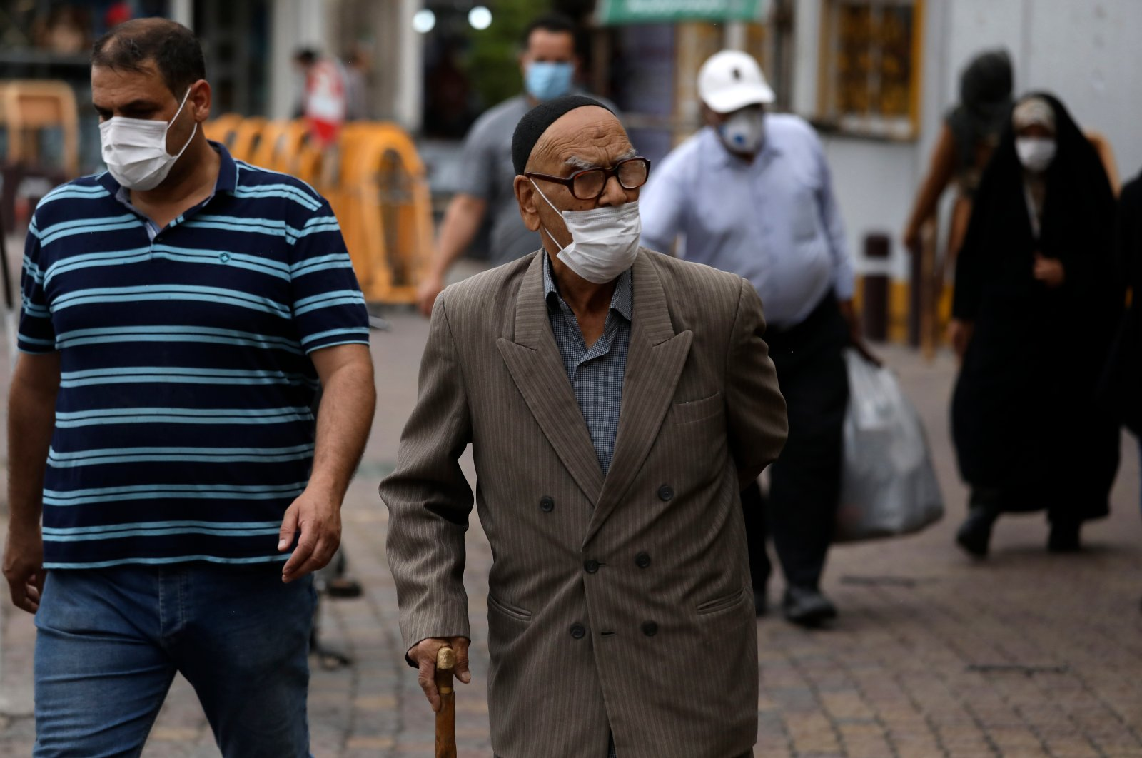 People wearing protective face masks to help prevent the spread of the coronavirus walk on a sidewalk in the city of Zanjan, some 330 kilometers (205 miles) west of the capital Tehran, Iran, Sunday, July 5, 2020. (AP Photo)