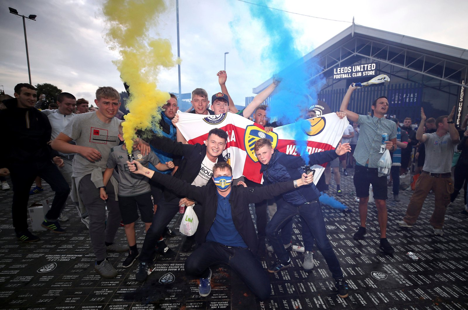 Leeds United fans celebrate outside Elland Road, Friday, July 17, 2020, in Leeds, England, after Huddersfield Town beat West Bromwich Albion to seal their promotion to the Premier League. (PA via AP)