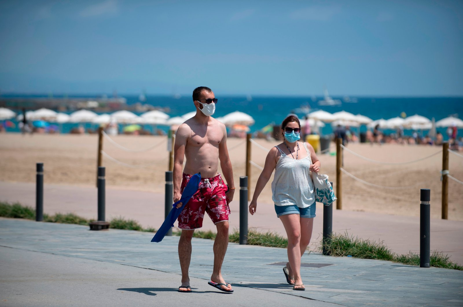 People wear face masks as they walk along a beach in Barcelona, July 18, 2020. (AFP Photo)