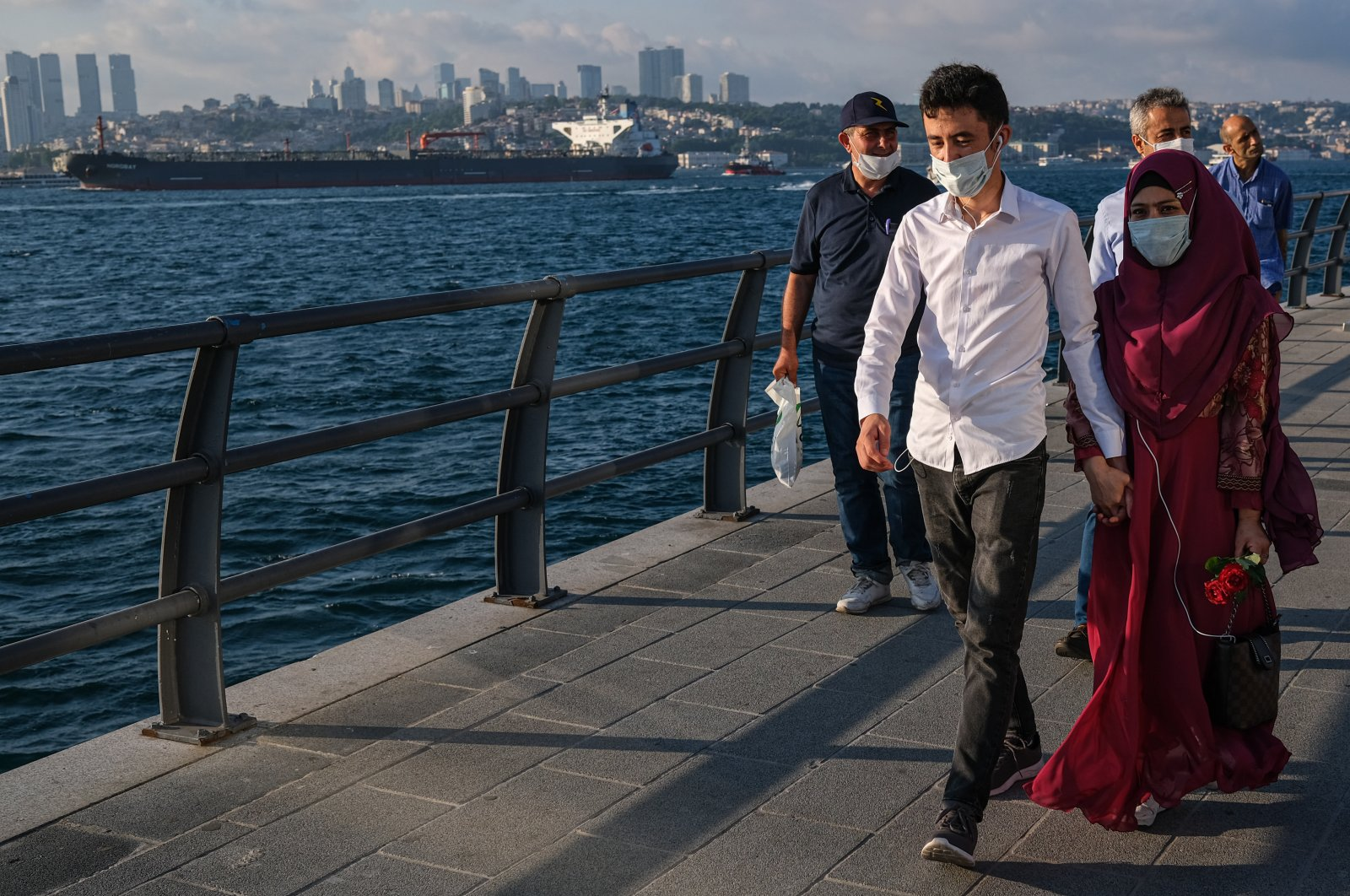 People walk near Bosporus, amid the ongoing coronavirus pandemic in Istanbul, July 5, 2020. (EPA Photo)