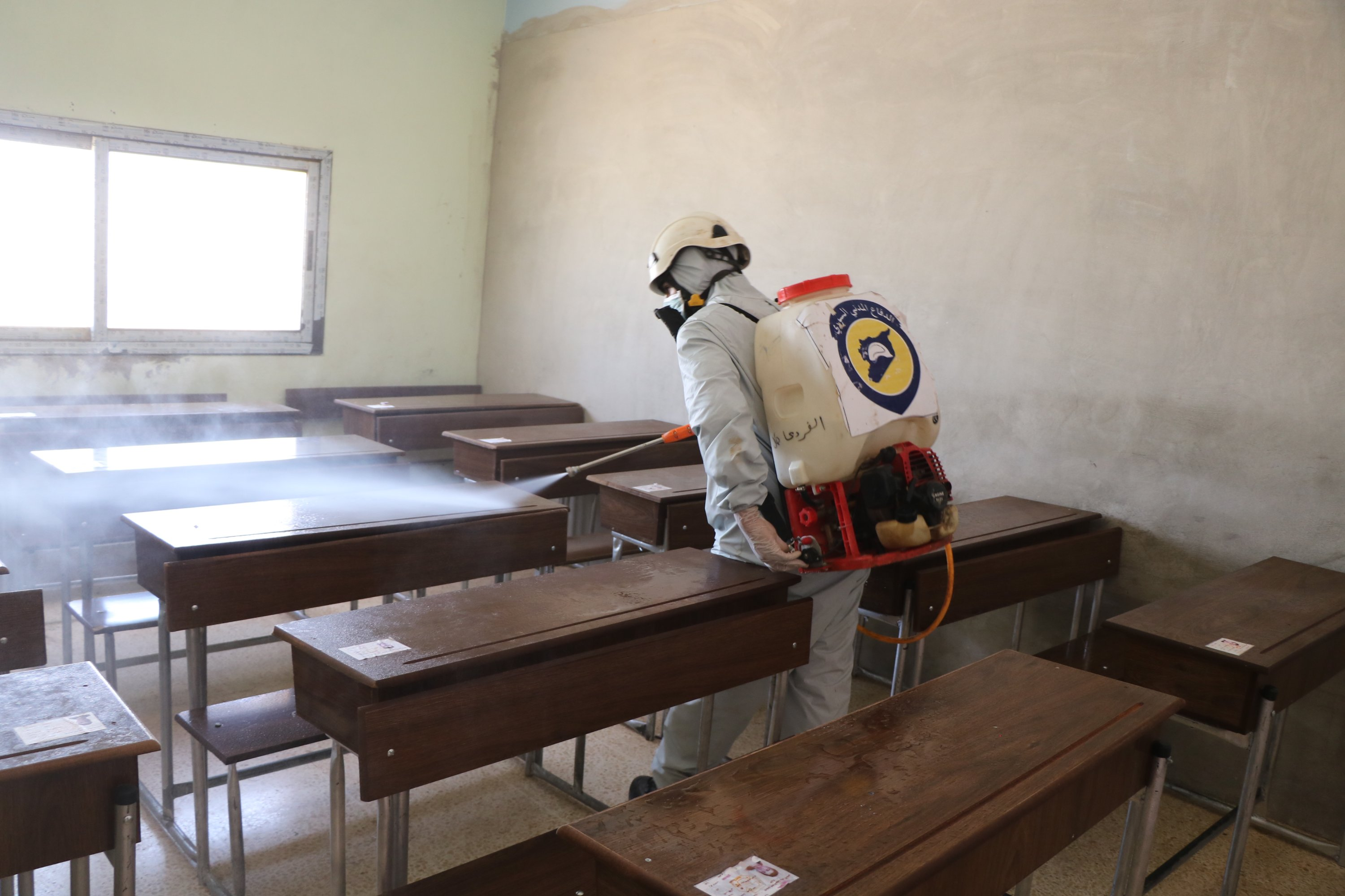 A White Helmets worker disinfects a school in Idlib as a measure against the coronavirus, July 15, 2020. (AA)