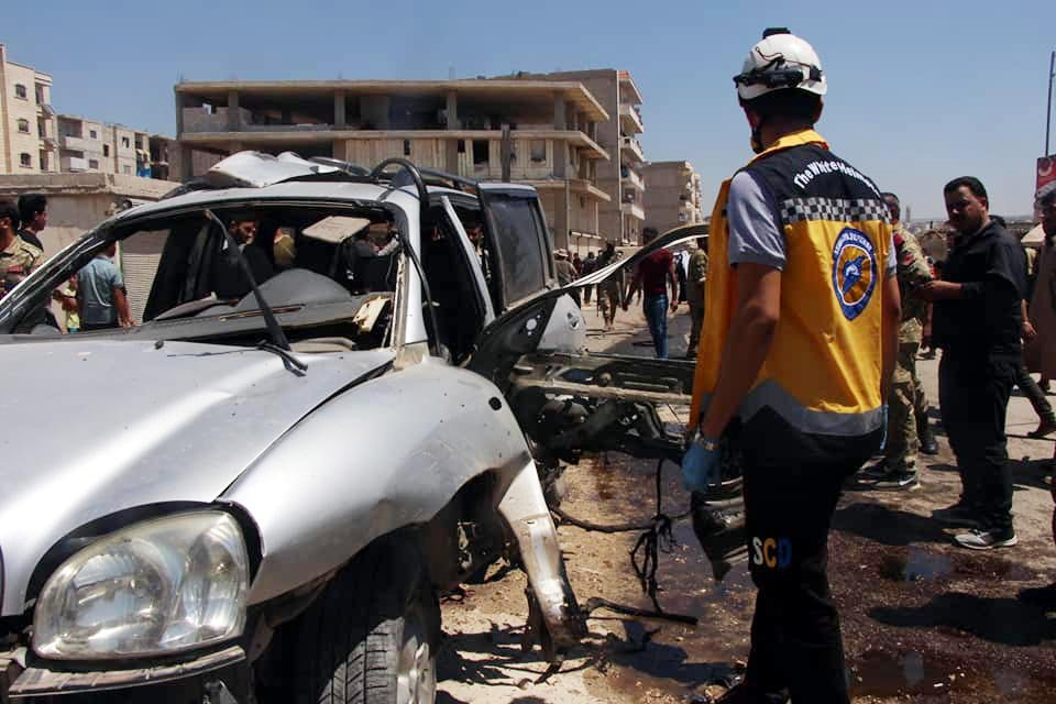 A vehicle damaged by a bomb and a member of the White Helmets civil defense group are seen in the district center of Afrin, Syria, July 19, 2020. (DHA Photo)
