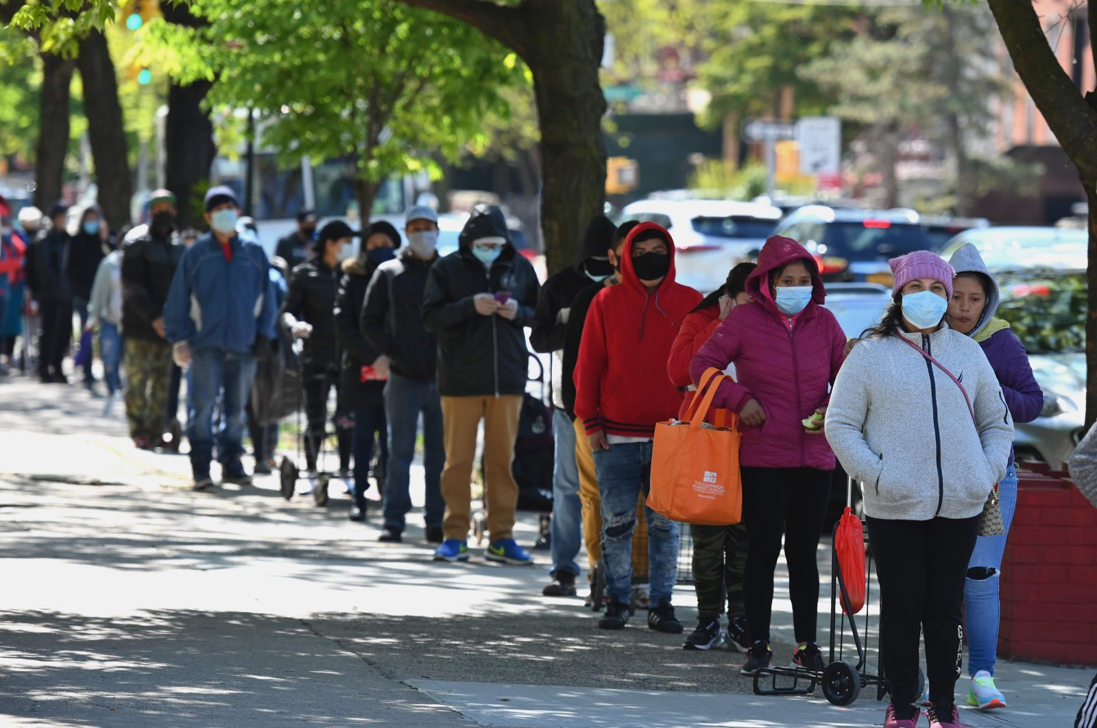People wait in line as members of the U.S. Army National Guard hand out food and other essentials for people in need at a food pantry in the Brooklyn borough of New York City, New York, U.S., May 13, 2020. (AFP Photo)