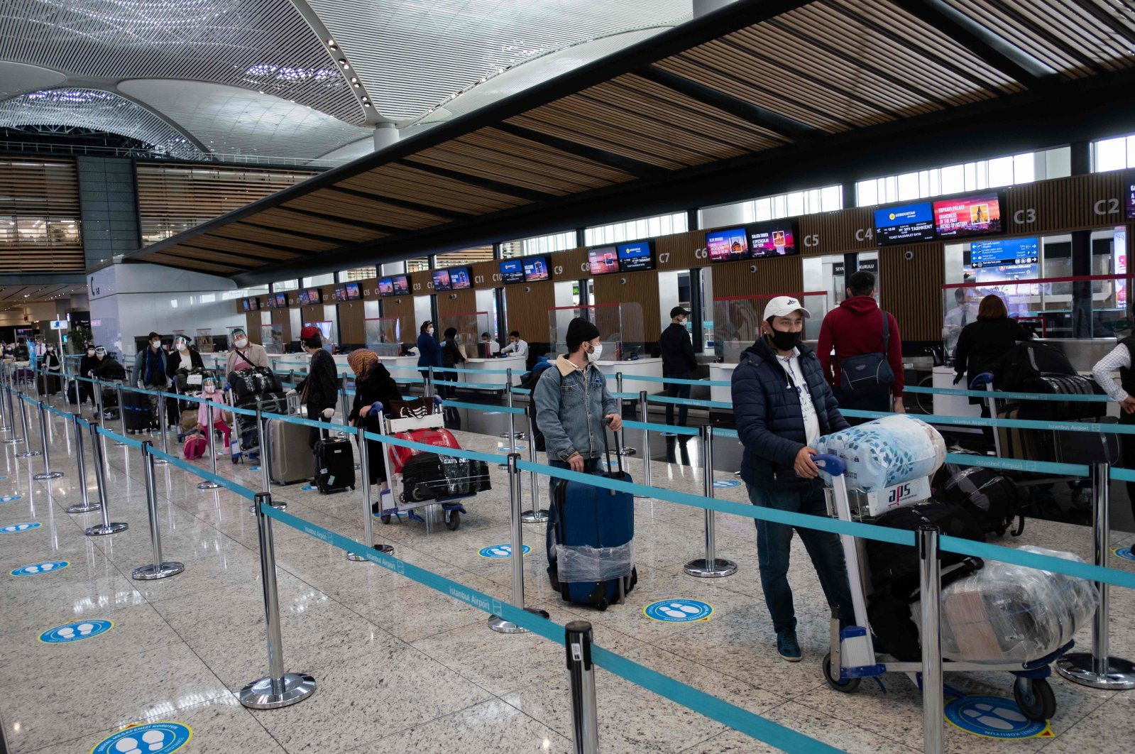 Passengers wearing protective face masks wait to be checked in at Istanbul Airport, June 1, 2020. (AFP Photo)