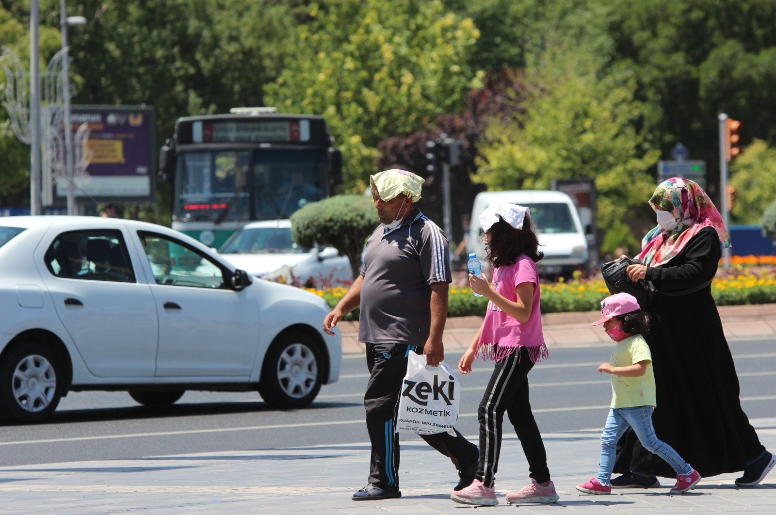 People shielding themselves from the sun cross the street in Kayseri, Turkey, July 19, 2020. (İHA Photo)