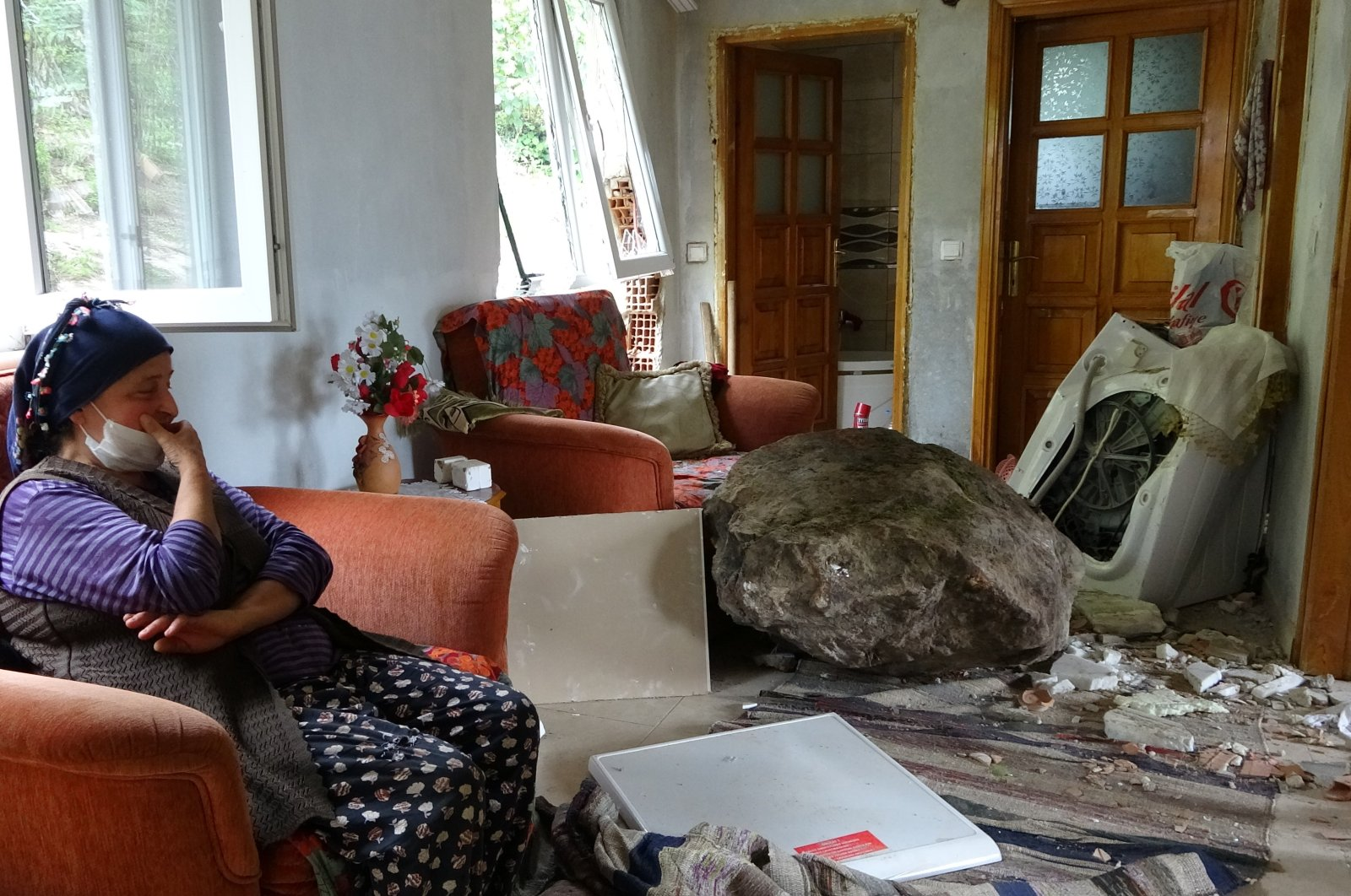 Inci Engin sits next to the rock that crashed into her house, in Ordu, Turkey, July 19, 2020. (İHA Photo)