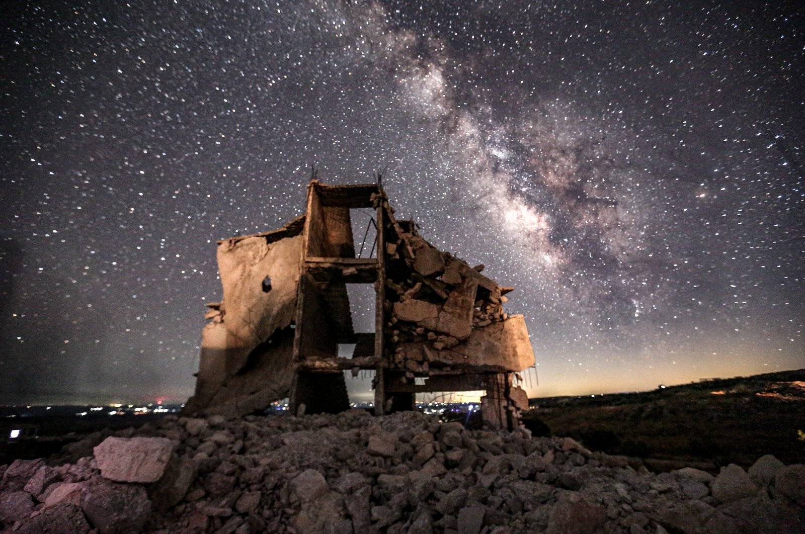 A building damaged by Syrian regime attacks shines under the stars in Idlib, July 18, 2020. (AA)