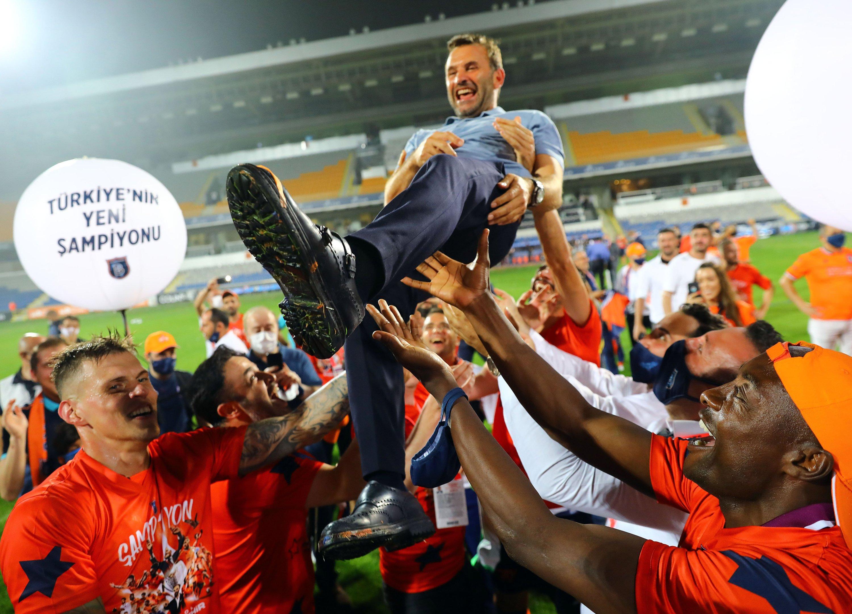Başakşehir players throw coach Okan Buruk in the air as they celebrate their Süper Lig championship, Istanbul, Turkey, July 19, 2020. (IHA Photo)
