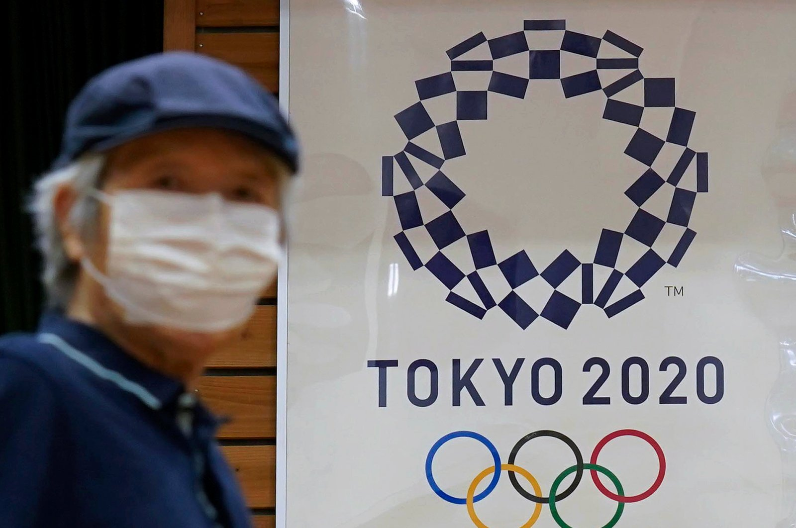 A man wears a face mask as he walks past a poster for Tokyo 2020 Olympics in Tokyo, Japan, July 5, 2020. (EPA Photo)