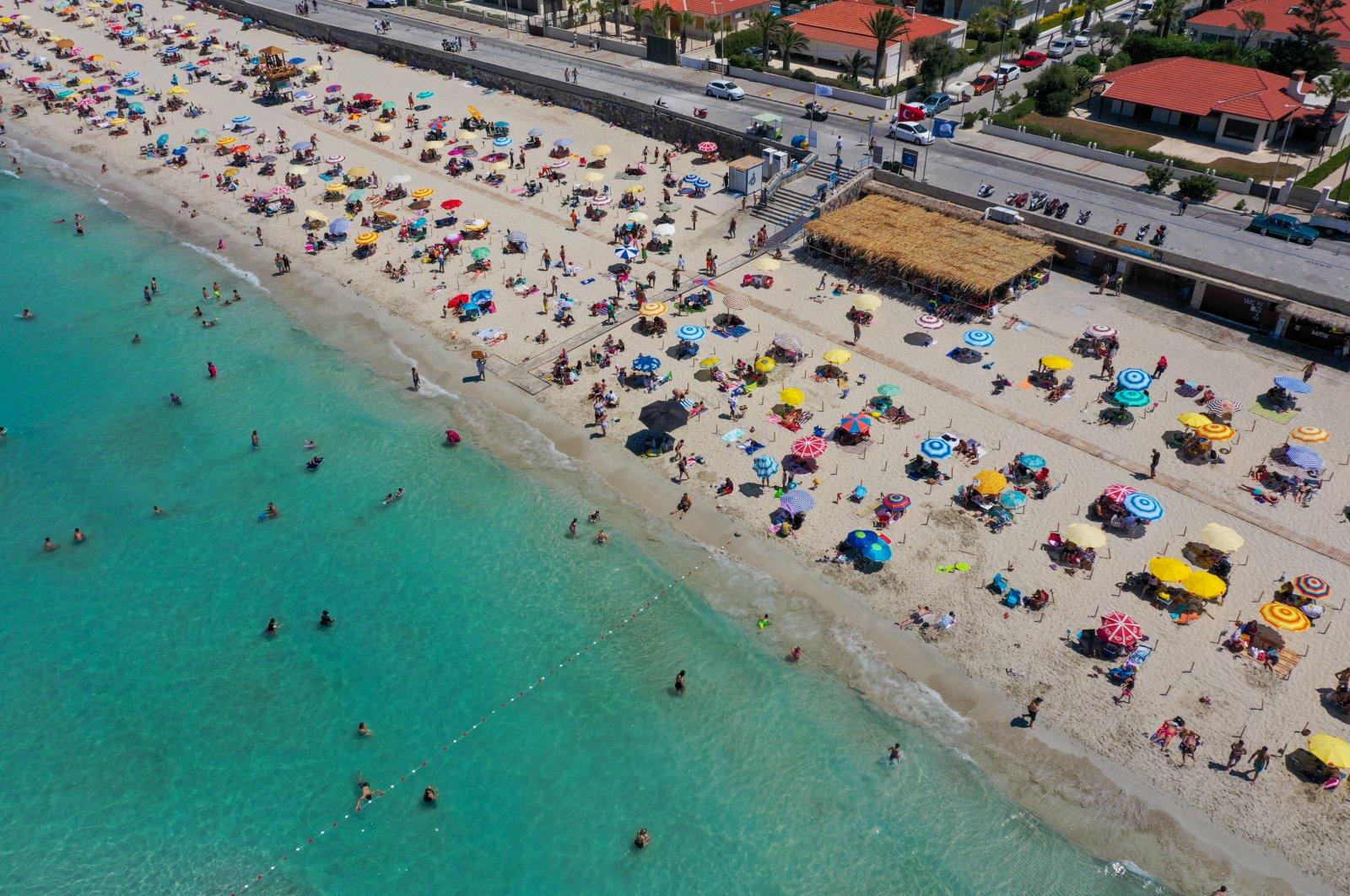 Tourists enjoy the sun at Ilıca Beach in Çeşme, a resort town west of Izmir, in Turkey's Aegean region, July 19, 2020. (AA Photo)