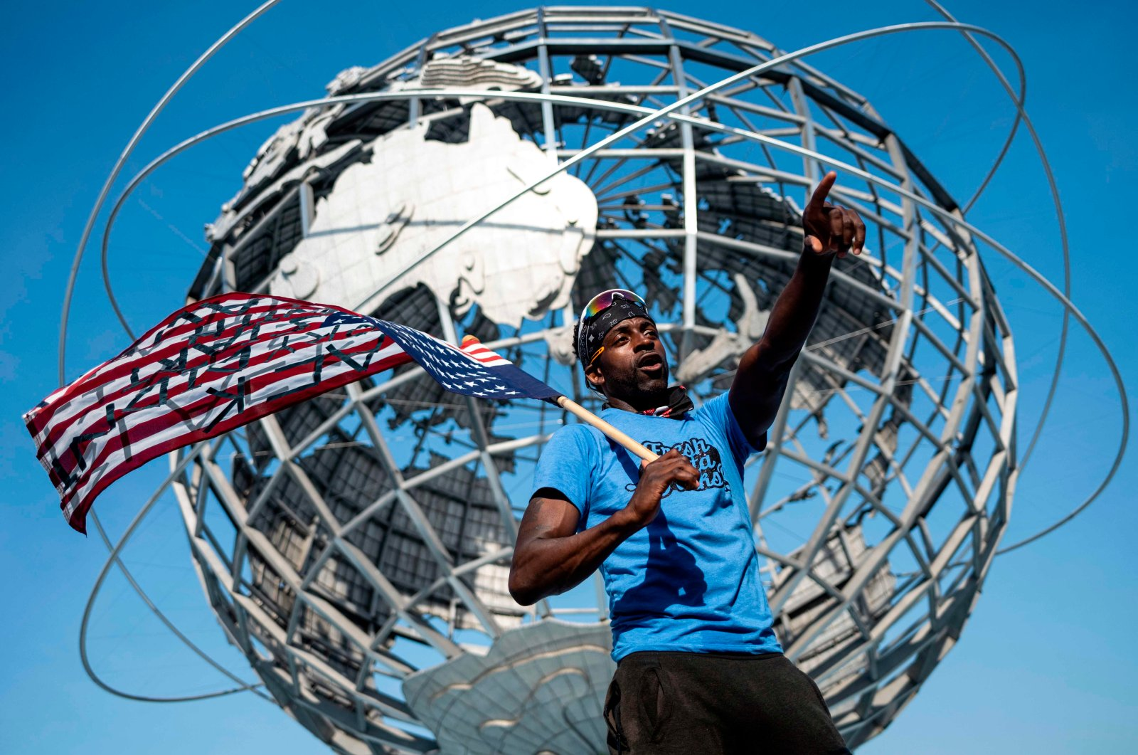 A protestor holds an upside-down American flag in front of the Unisphere during a Justice Ride, protesting the death of George Floyd, in the Flushing Meadows-Corona Park in the borough of Queens, New York City, July 18, 2020. (AFP Photo)