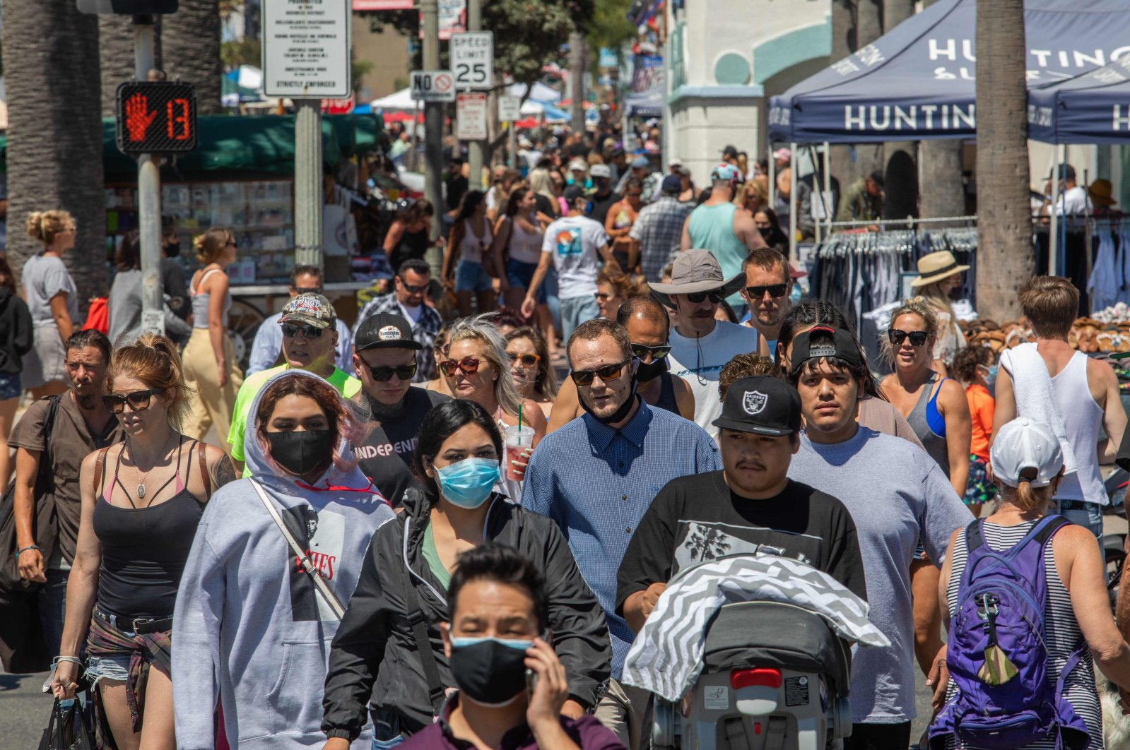 People cross the street in Huntington Beach, California, amid the coronavirus pandemic, July 19, 2020. (AFP Photo)