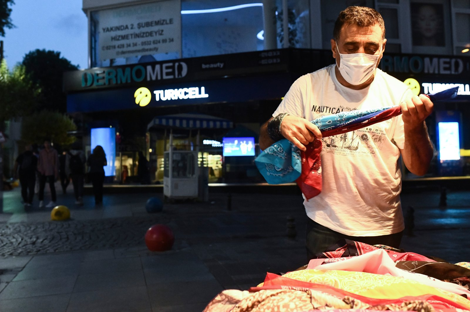 A vendor, wearing a face mask to prevent the spread of the coronavirus, stands outside his shop in Istanbul, Turkey, July 19, 2020. (AP Photo)