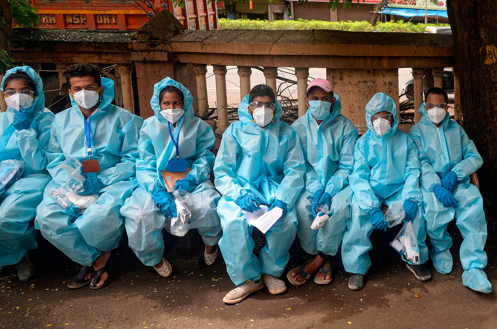 Health workers wait for instructions to conduct a door-to-door medical screening drive for COVID-19 coronavirus, Mumbai. July 20, 2020. (AP Photo)