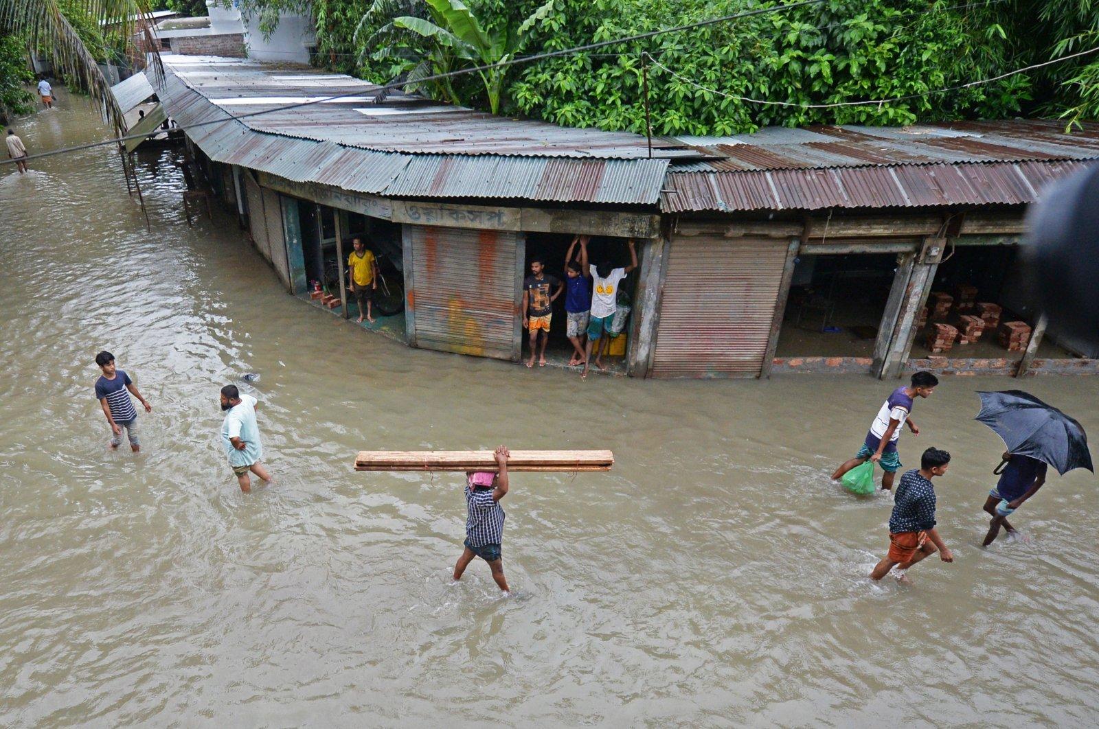 People wade through a flooded street in Sreenagar, Munshiganj, Bangladesh, July 20, 2020. (AFP Photo)