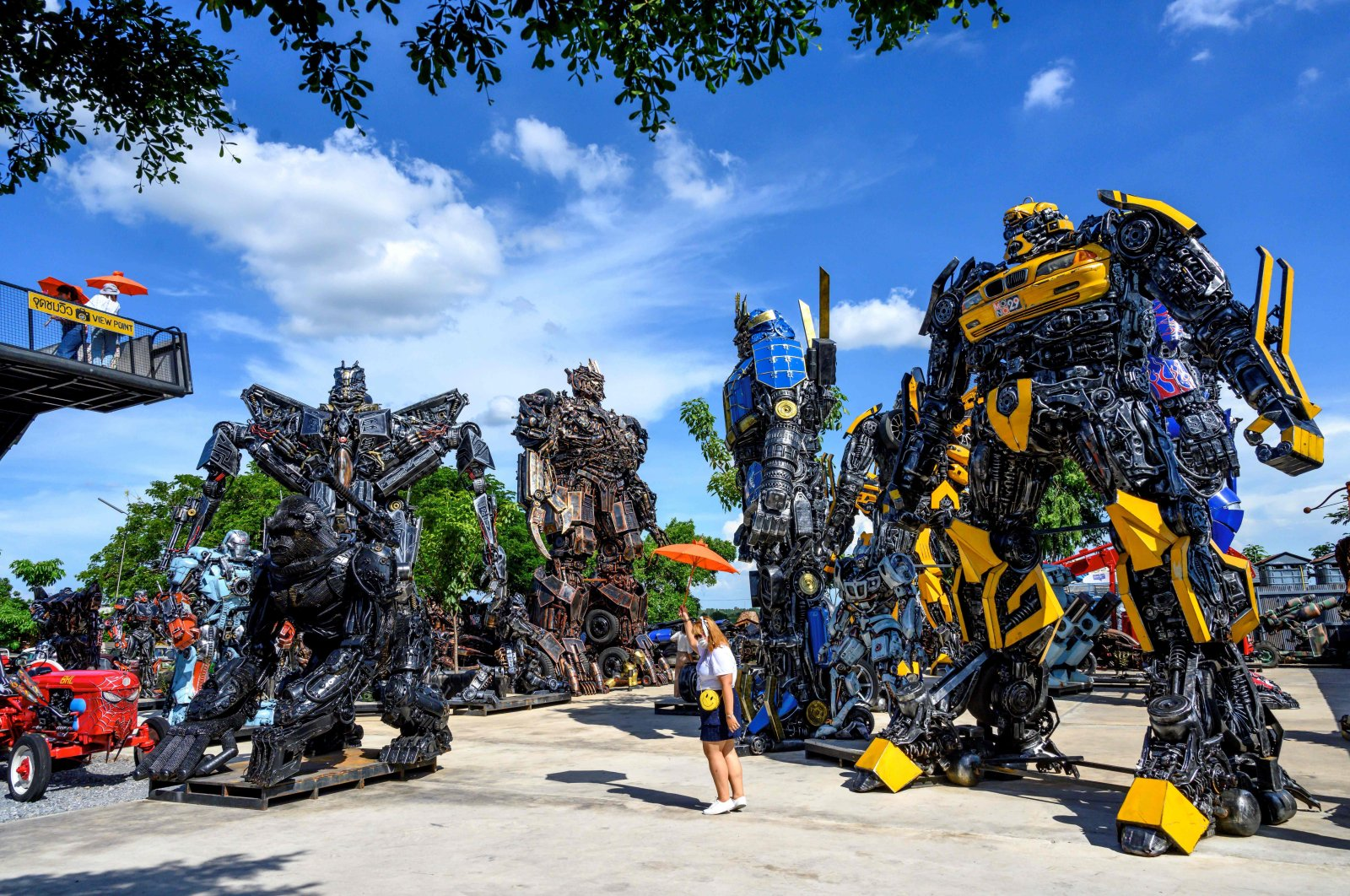 """Tourists take photos of life-sized sculptures of characters from the """"Transformers"""" film franchise made of scrap metal parts at the Ban Hun Lek museum in Ang Thong, Thailand, July 18, 2020. (AFP PHOTO)"""