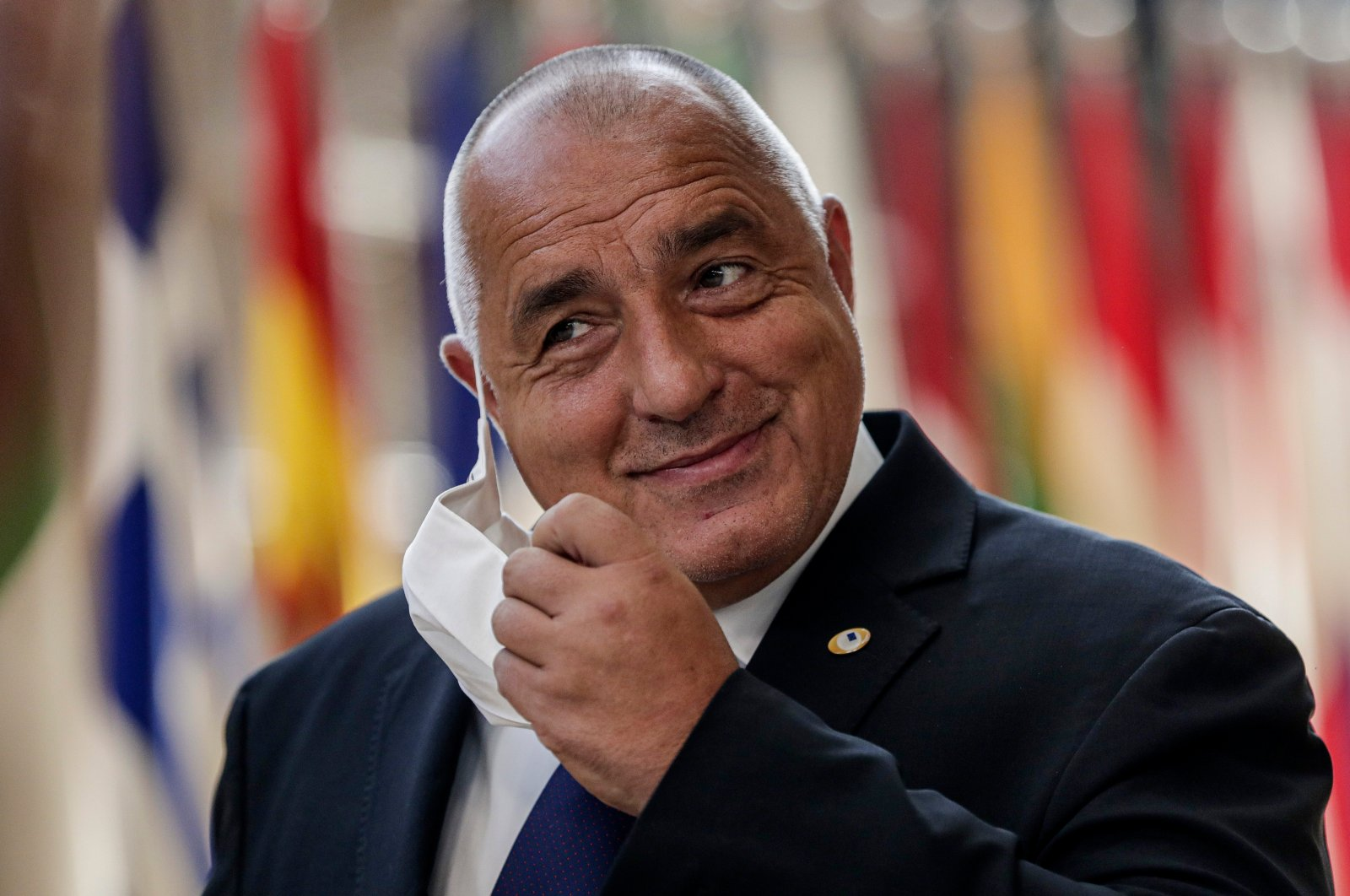 Bulgaria's Prime Minister Boyko Borissov takes off his protective face mask as he arrives for an EU summit at the European Council building in Brussels, July 18, 2020. (AP Photo)