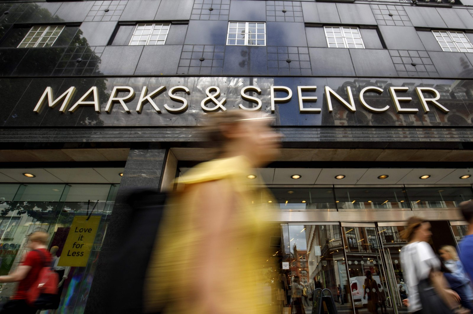 Shoppers walk past a Marks & Spencer shop on Oxford Street in central London, June 19, 2018. (AFP Photo)