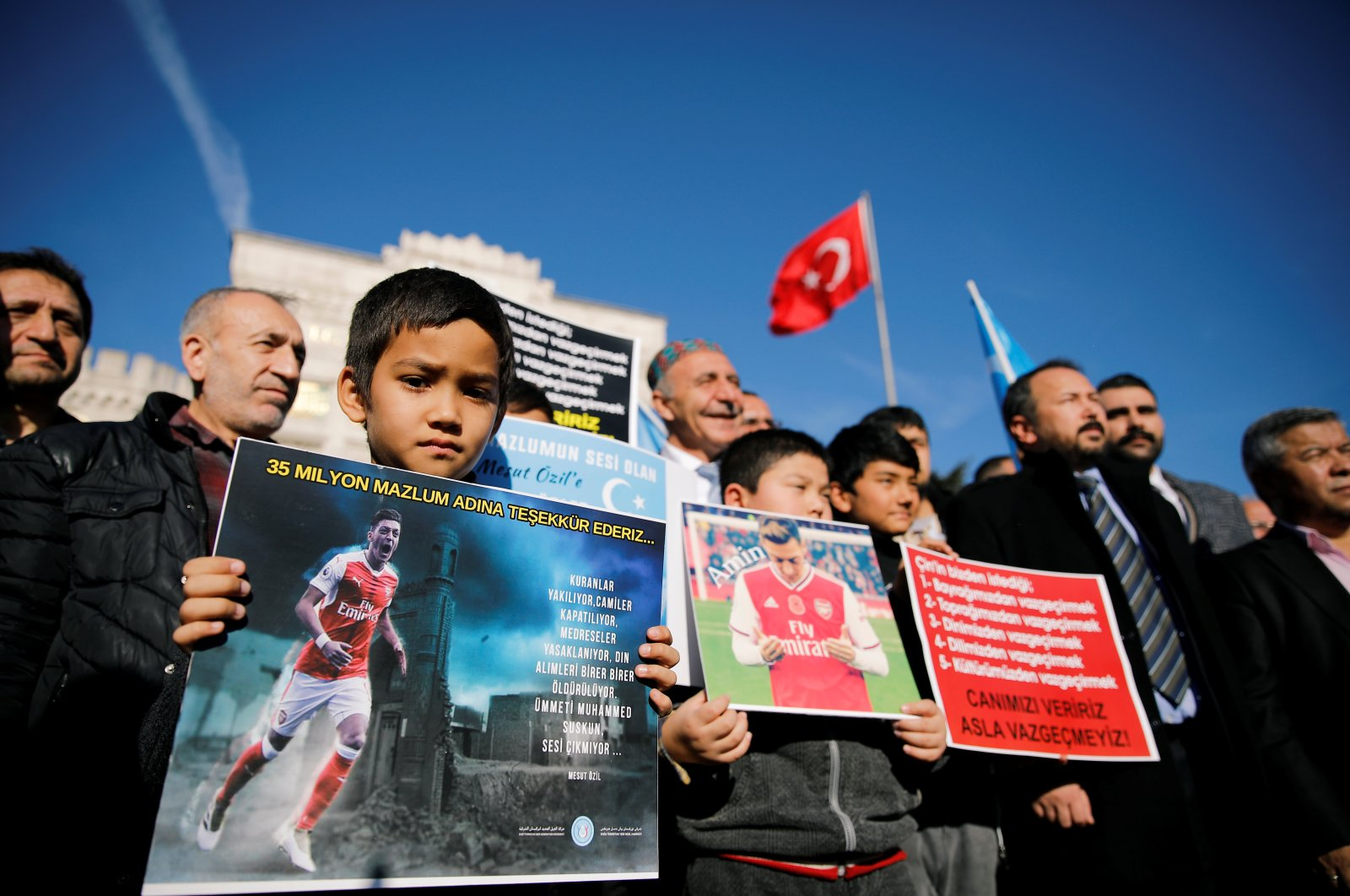 Uighur boys hold placards with the pictures of English soccer club Arsenal's midfielder Mesut Özil during a protest against China in Istanbul, Turkey, Dec. 14, 2019. (REUTERS Photo)