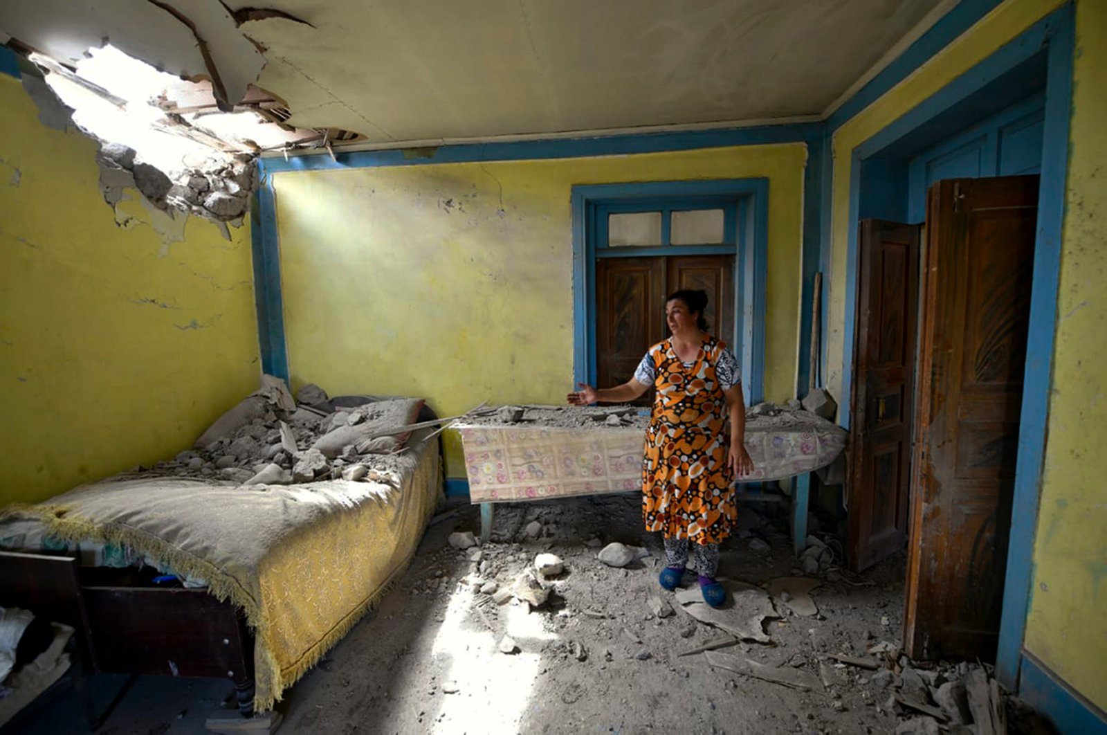 A woman shows damage to her house after shelling by Armenian forces in the Tovuz region of Azerbaijan, July 14, 2020. (AP Photo)