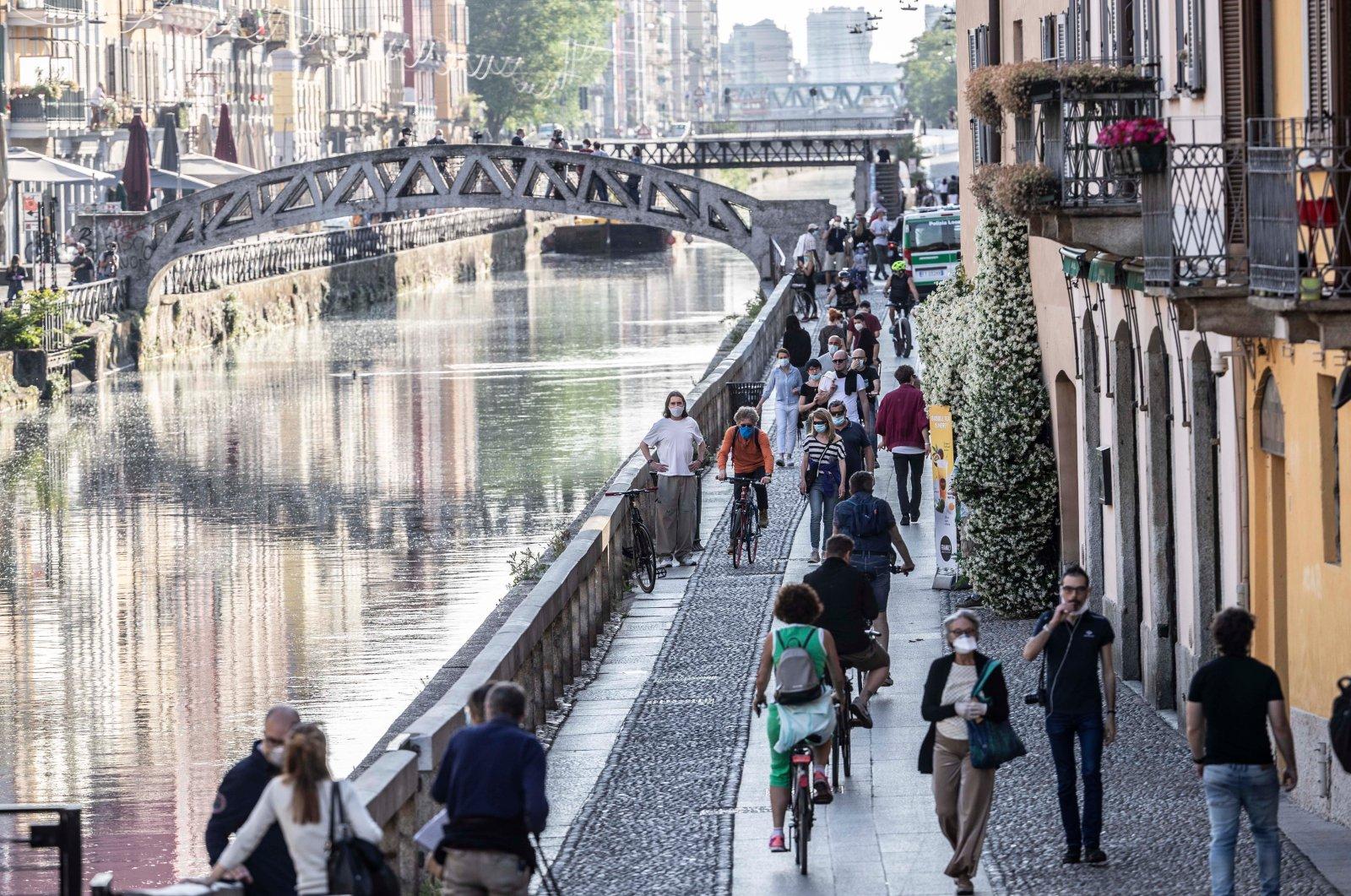 People walk along the popular Navigli area during the coronavirus outbreak, Milan, Italy, May 8, 2020. (AP Photo)