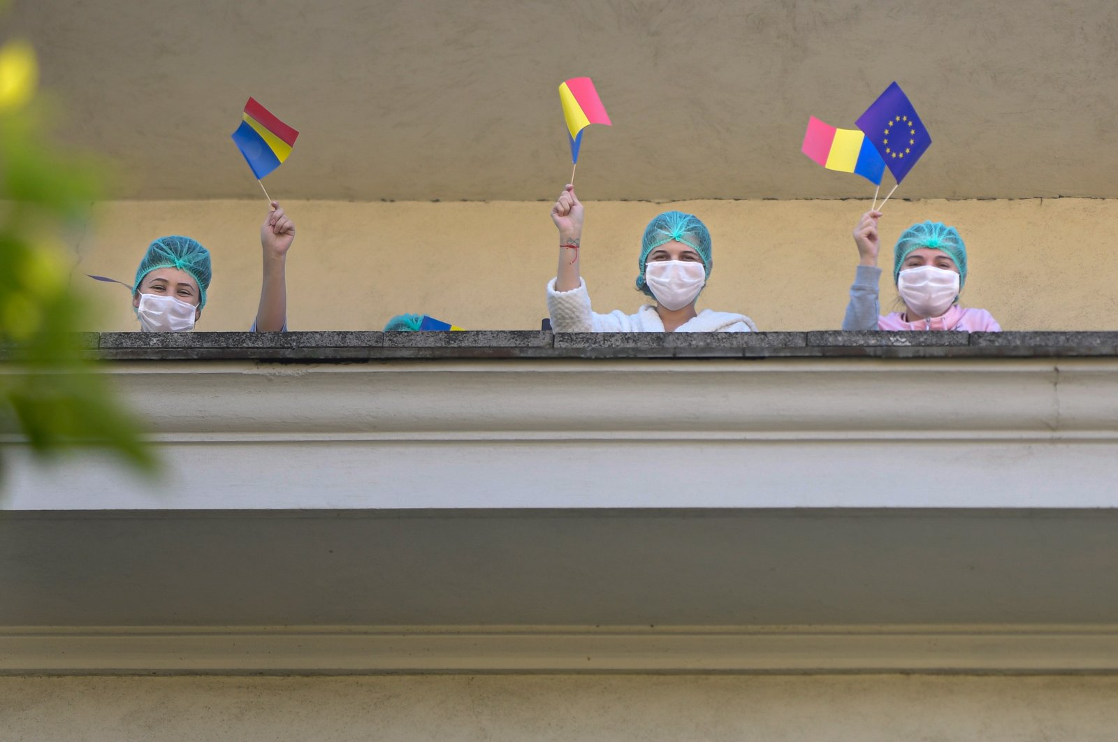 Medical staff of the Polizu maternity hospital hold European Union and Romanian flags while listening to a violinist playing to entertain them and the patients in Bucharest, Romania, Tuesday, April 28, 2020. (AP Photo)