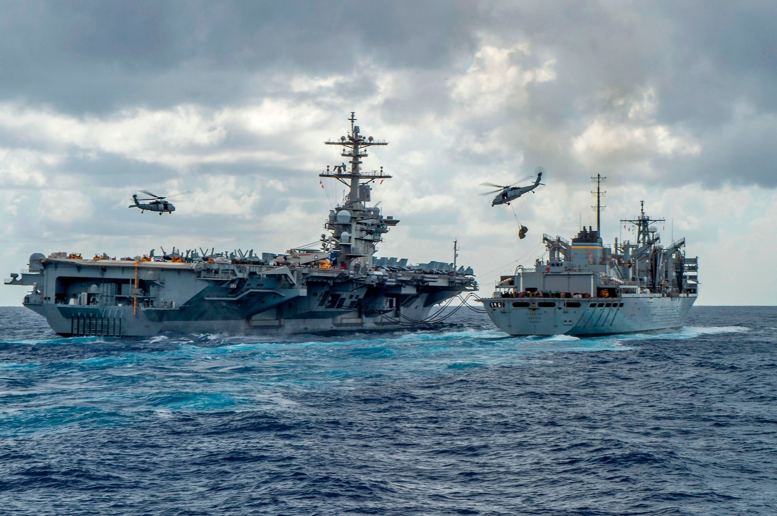"""The Nimitz-class aircraft carrier USS Abraham Lincoln (CVN 72) conducts a replenishment-at-sea with the fast combat support ship USNS Arctic (T-AOE 9), while MH-60S Sea Hawk helicopters assigned to the """"Nightdippers"""" of Helicopter Maritime Strike Squadron (HSM) 5 transfer stores between the ships, in this handout photo released by the U.S. Navy on May 8, 2019. (AFP Photo)"""