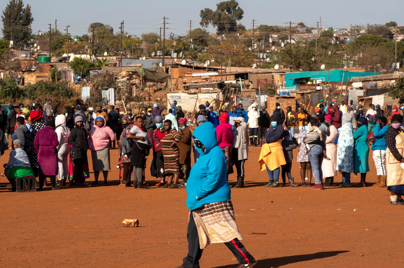 A woman walks across a dusty soccer field as people affected by the coronavirus' economic downturn line up to receive food donations, Pretoria, South Africa, May 20, 2020. (AP Photo)