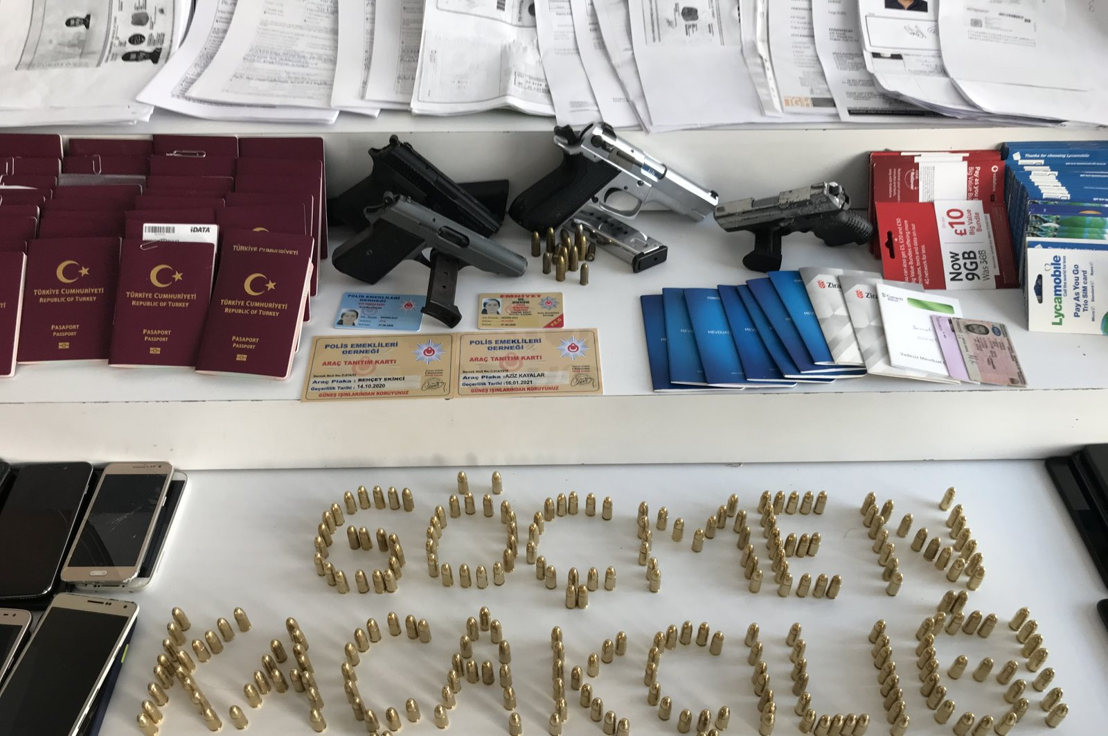 "Passports, guns and other materials seized from the ""Kabataşlar"" gang on display at police headquarters in Istanbul, Turkey, July 21, 2020. (AA Photo)"