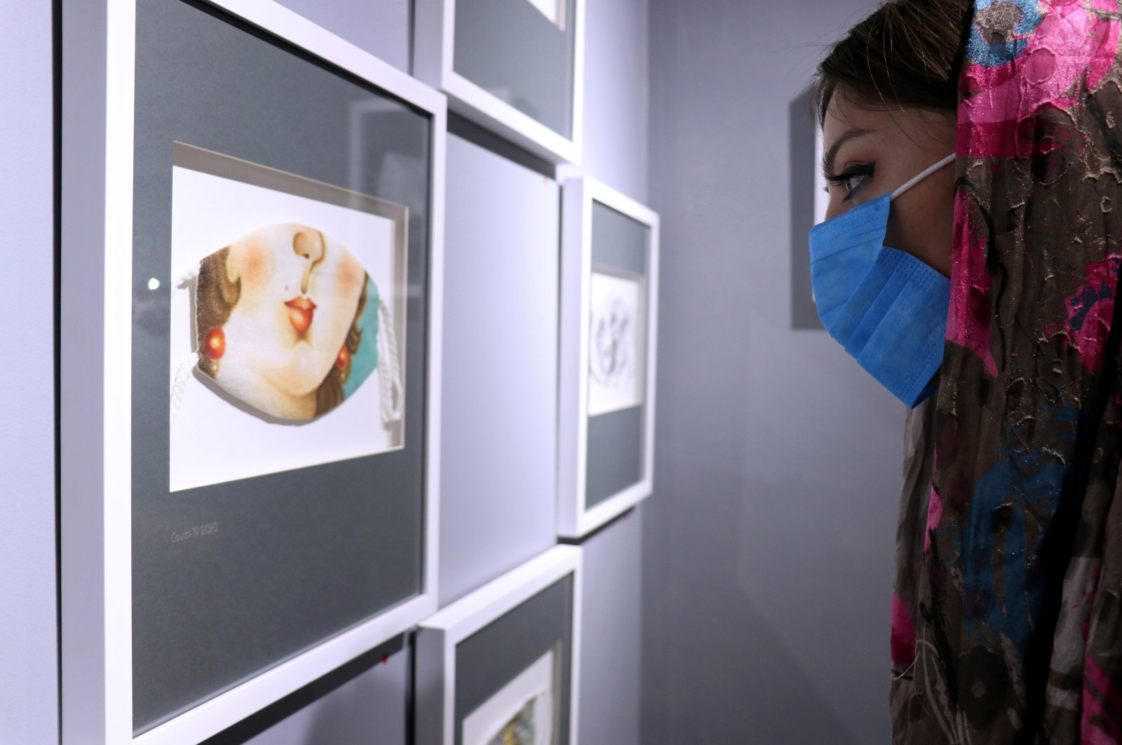 A woman looks at mask-themed artwork on display in an exhibition, following the outbreak of the coronavirus disease, in Tehran, July 18, 2020. (REUTERS)
