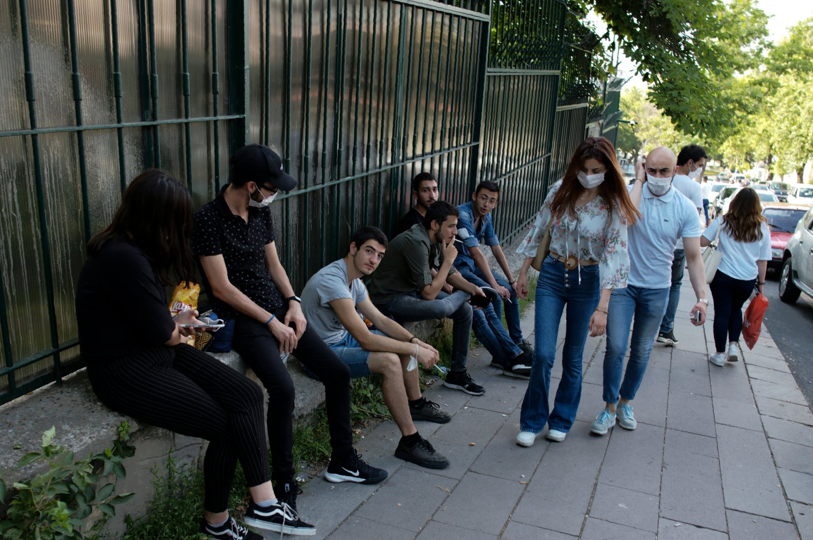 People wearing face masks to protect against the spread of coronavirus, walk past others without face coverings, in Ankara, Monday, June 29, 2020. (AP Photo)