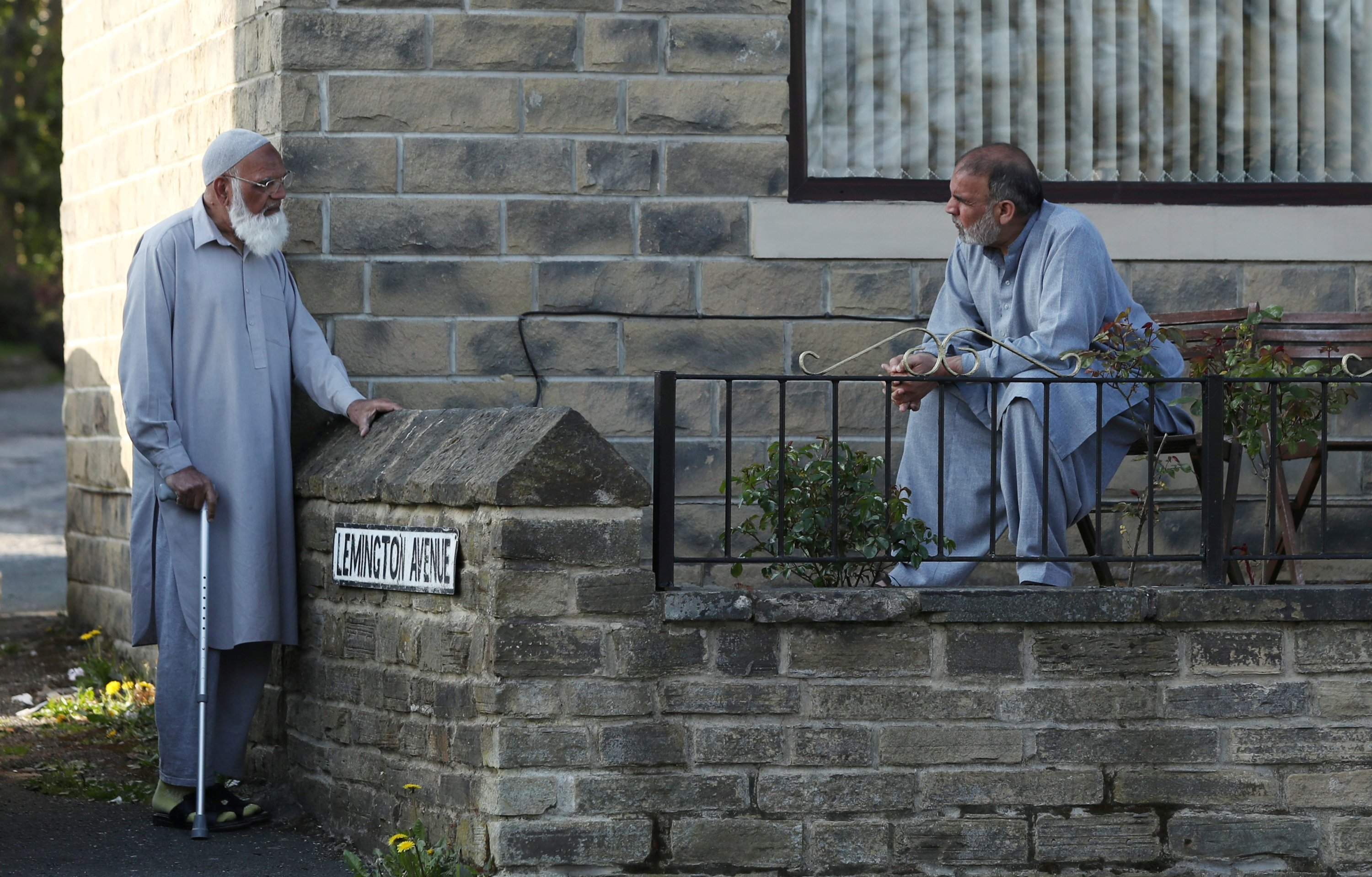 Two people chat while maintaining social distancing between them in Halifax, Britain, April 16, 2020. (REUTERS Photo=