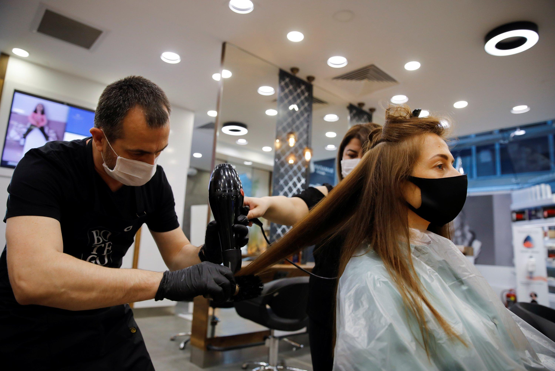 Hairdresser Oğuz Kutlu gives hair treatment to his customer Elena Kuznetsova in Istanbul, Turkey, May 11, 2020. (REUTERS Photo)