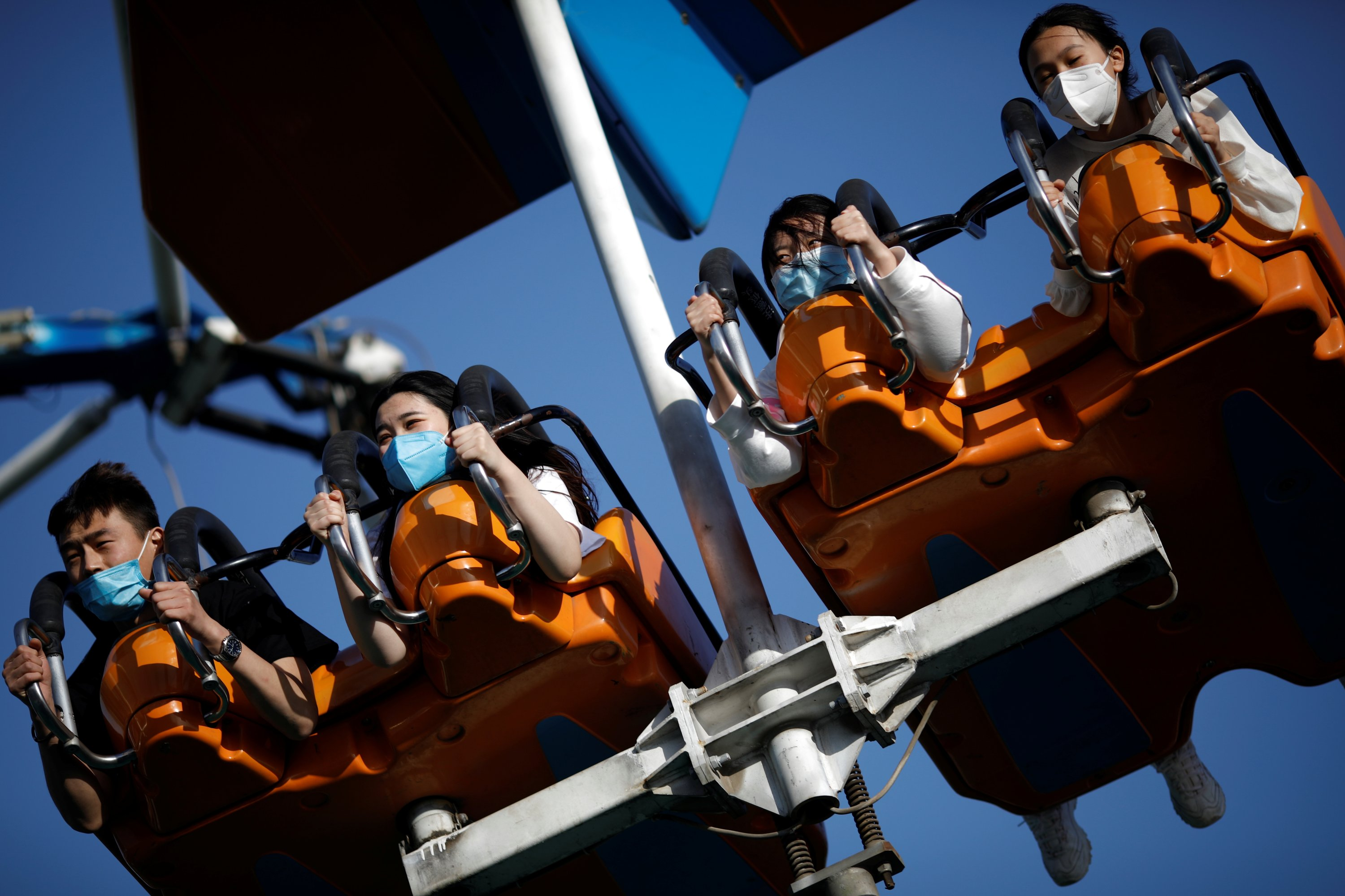 People wearing face masks enjoy an attraction at the Happy Valley amusement park in Beijing, China May 10, 2020. (REUTERS Photo)