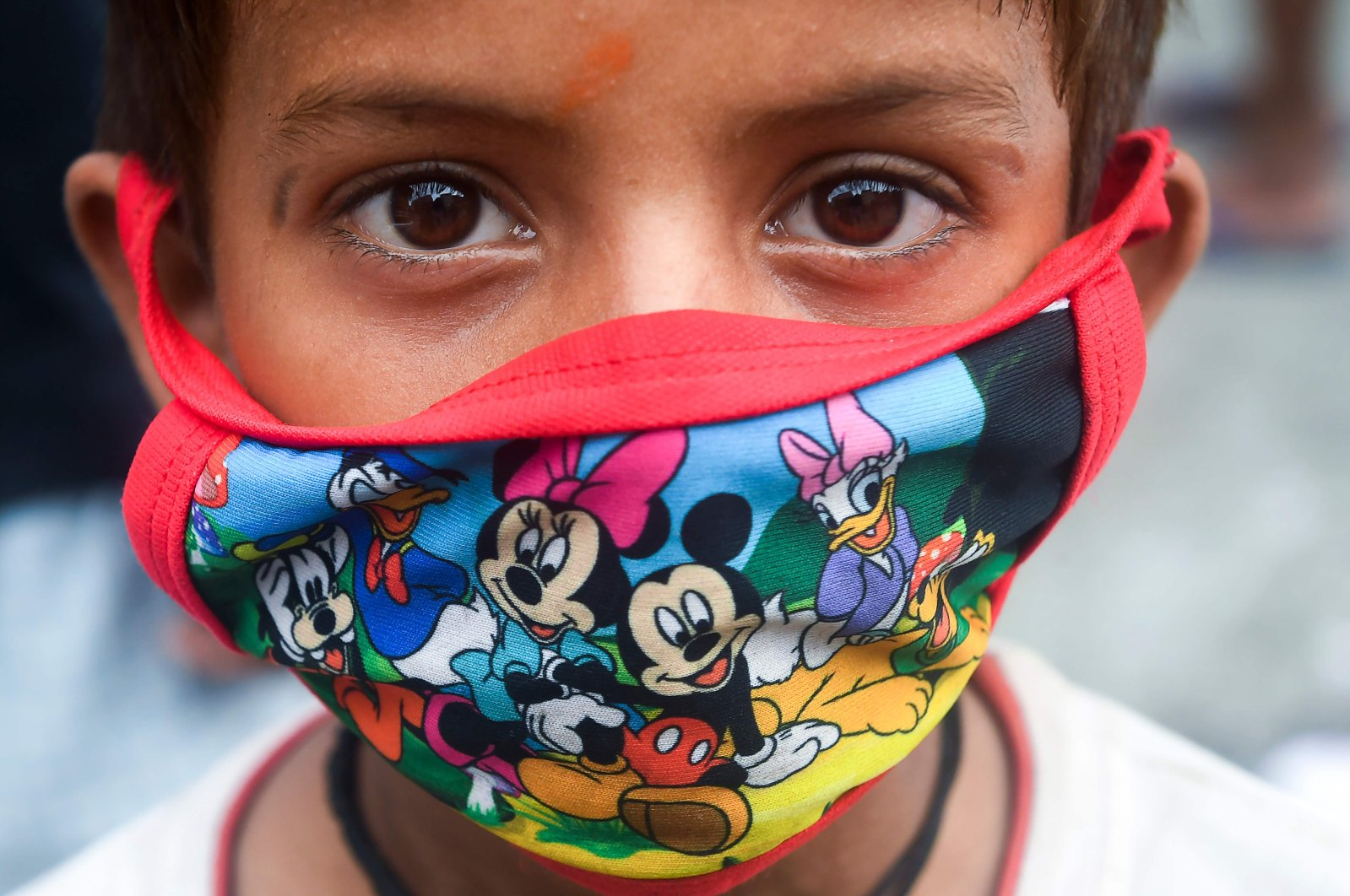 A child wears a face mask depicting Disney characters amid concerns over the spread of the coronavirus, in Kolkata, India, July 21, 2020. (AFP Photo)
