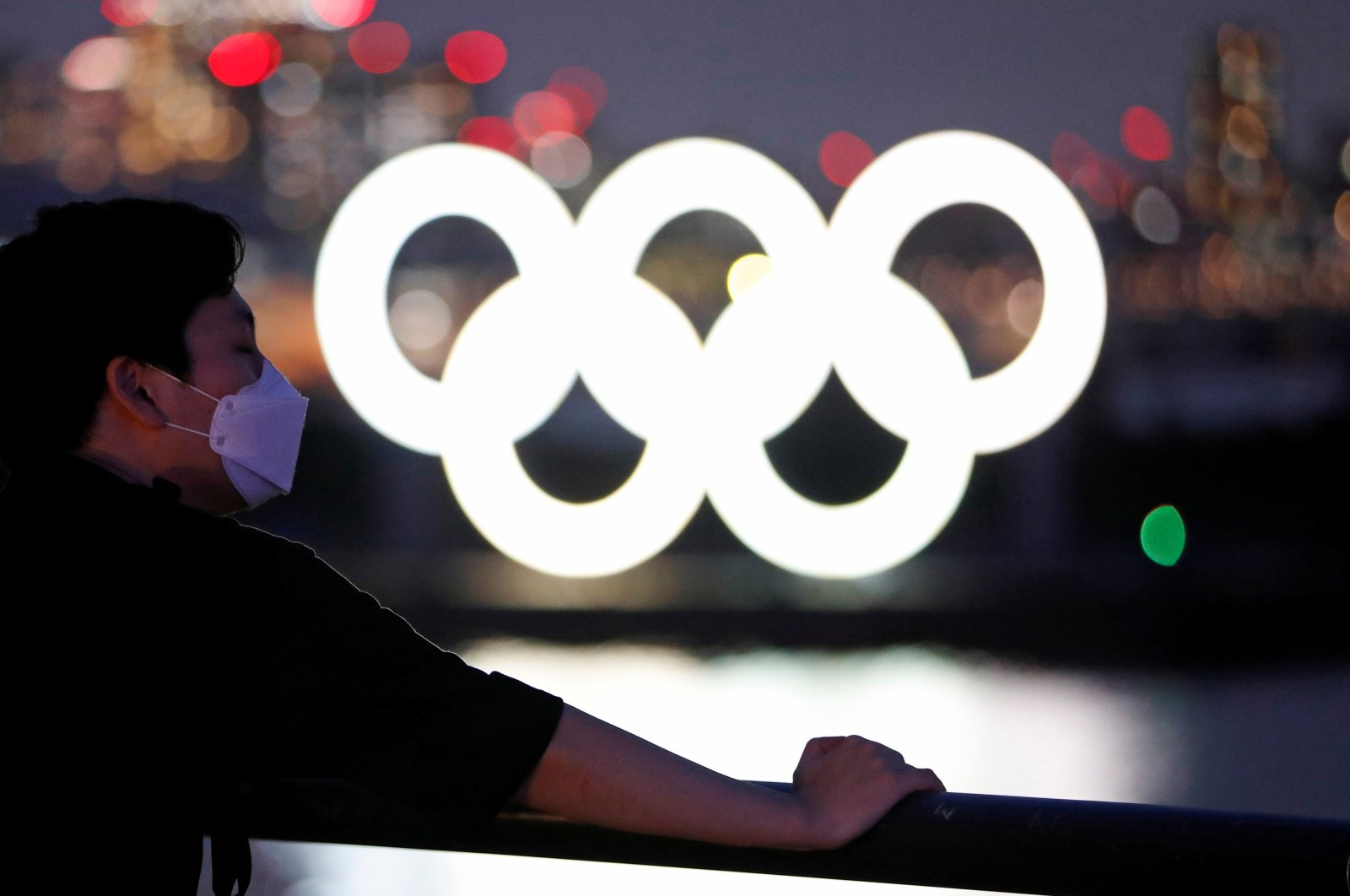 A man wearing a mask stands in the waterfront area in Odaiba Marine Park with the Olympic rings in the background, Tokyo, Japan, July 21, 2020. (Reuters Photo)