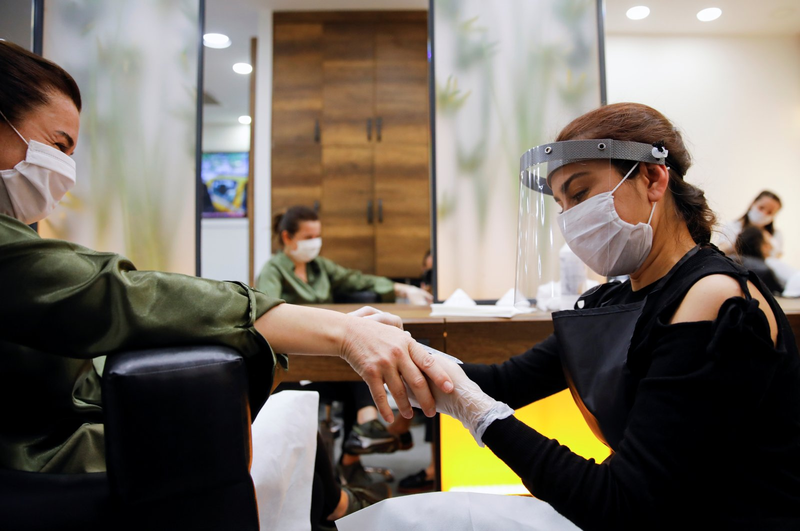 An employee gives manicure to her customer Pınar Ersin, both wearing protective masks in Istanbul, Turkey, May 11, 2020. (REUTERS Photo)