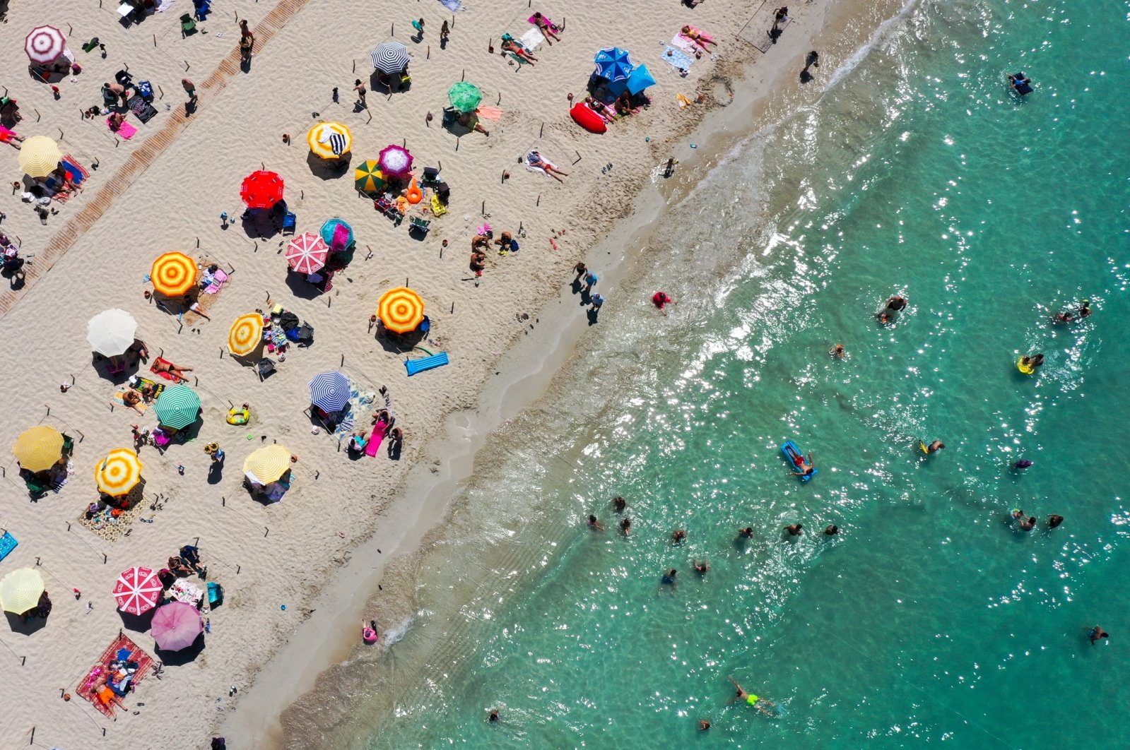 People enjoy the sun at Ilıca Beach in Çeşme, a resort town west of Izmir, in Turkey's Aegean region, July 19, 2020. (AA Photo)