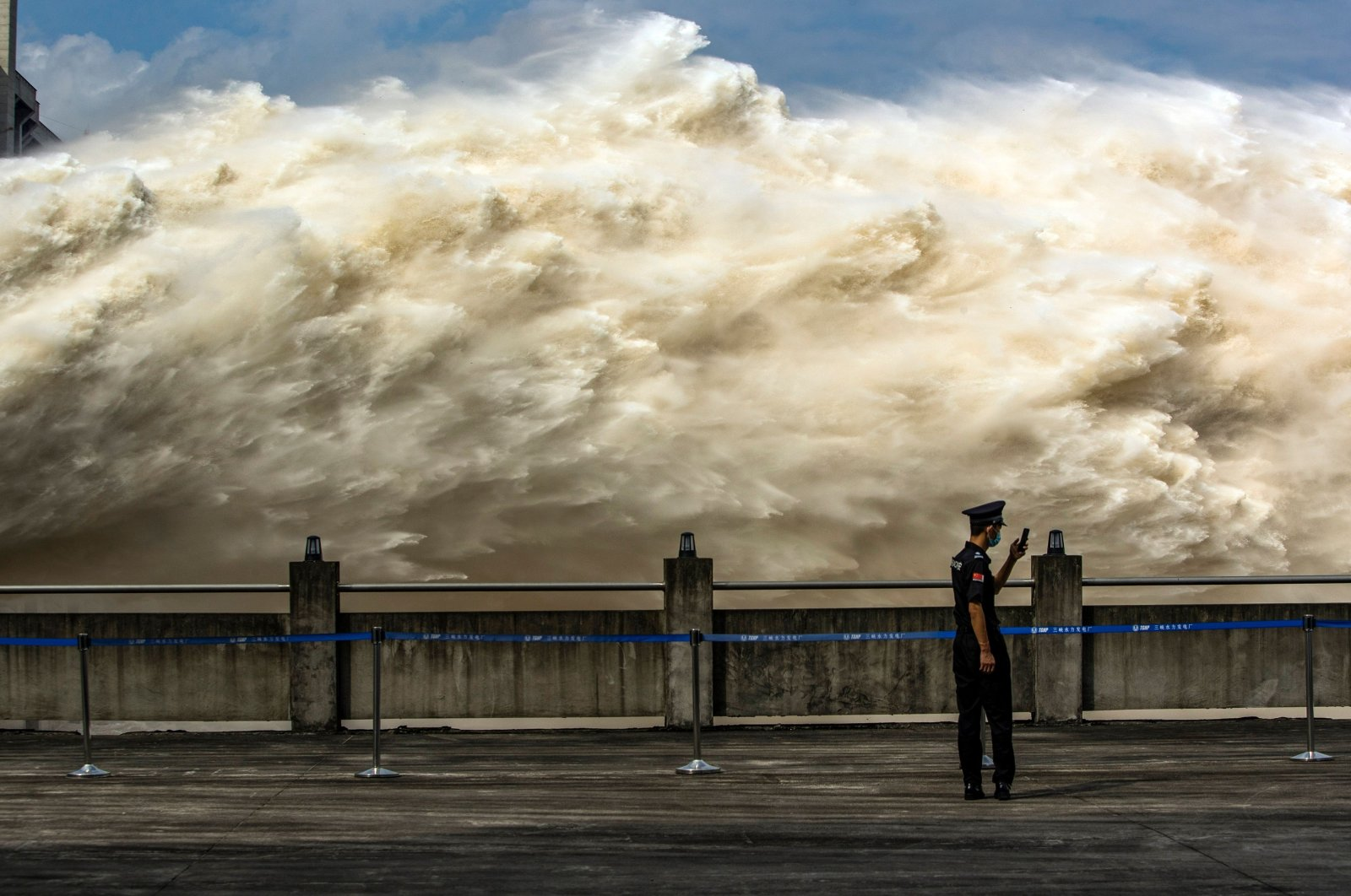 A security guard looking at his smartphone while water is released from the Three Gorges Dam, a gigantic hydropower project on the Yangtze river, to relieve flood pressure in Yichang, central China's Hubei province, July 19, 2020. (AFP Photo)