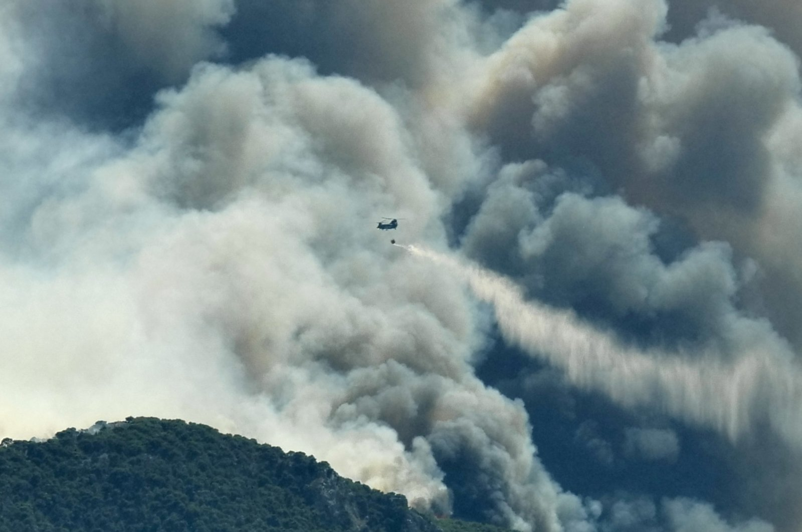 A Chinook helicopter makes a water drop as a wildfire burns near the village of Kechries, Greece, July 22, 2020. (Reuters Photo)